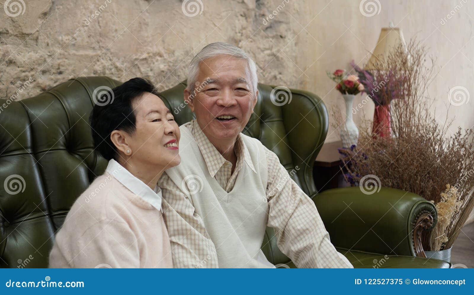 富有的亚裔资深父母在豪华美丽的房子backgrou坐
