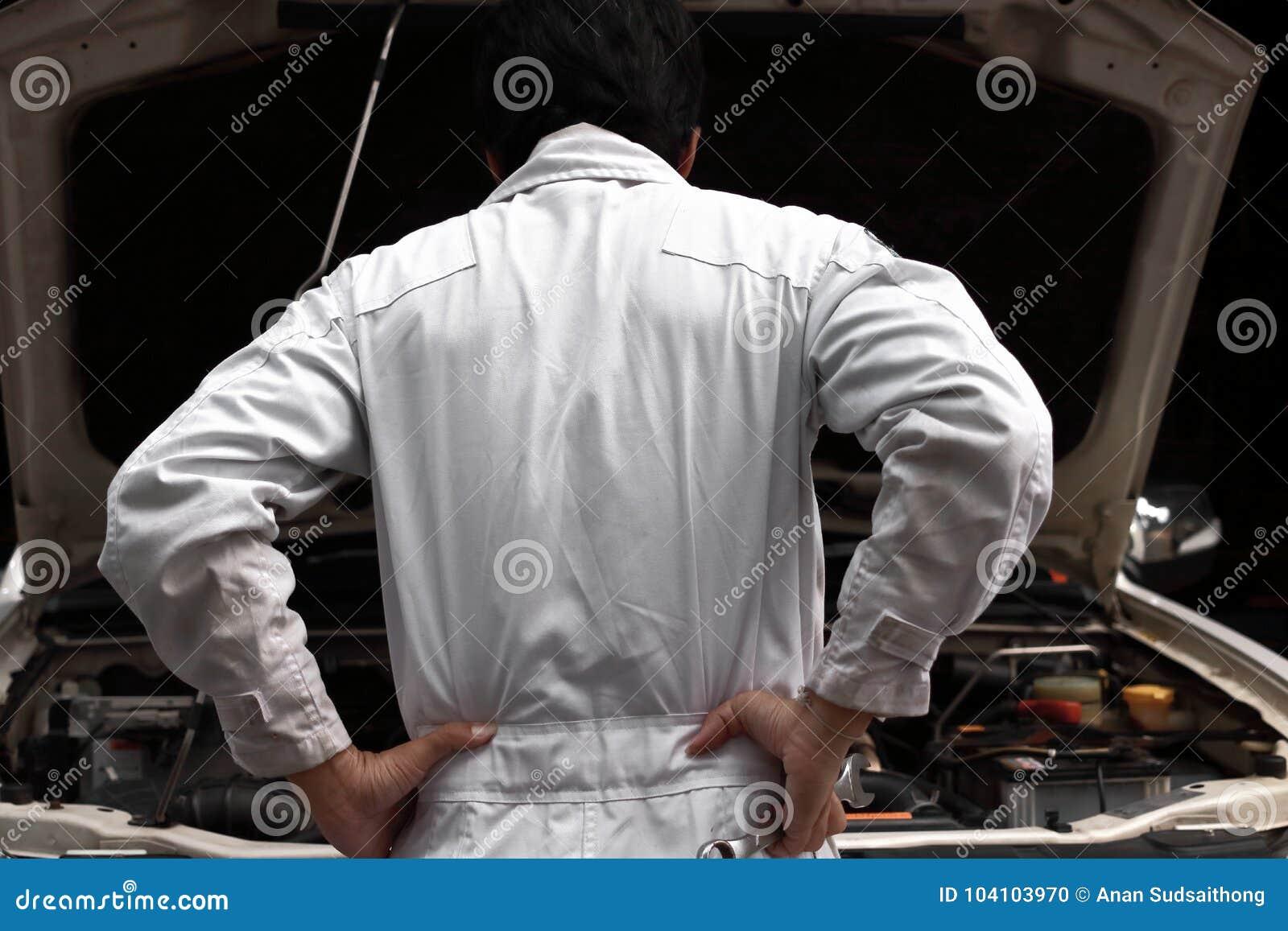 对在开放敞篷的汽车失望或用尽的白色一致的感觉的沮丧的被注重的年轻技工人在修理gara