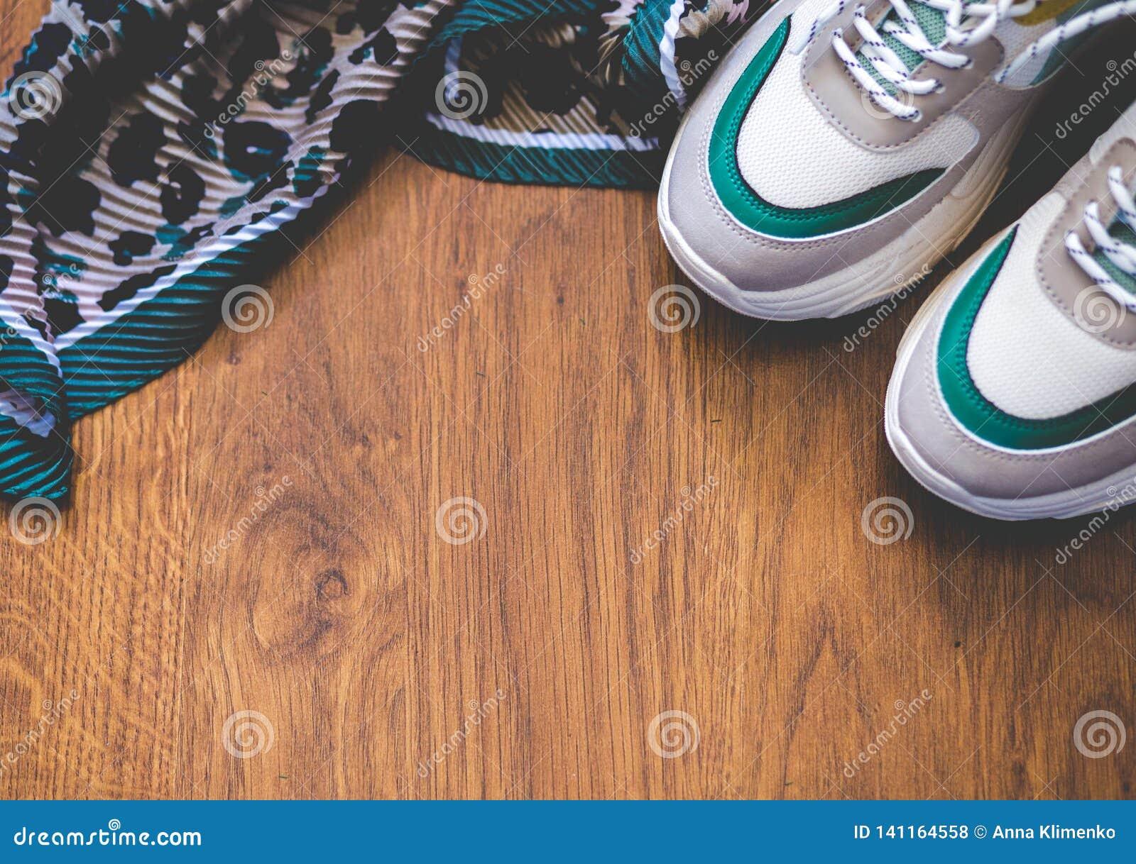 对在木背景的体育鞋子 新的运动鞋和空间广告文本的