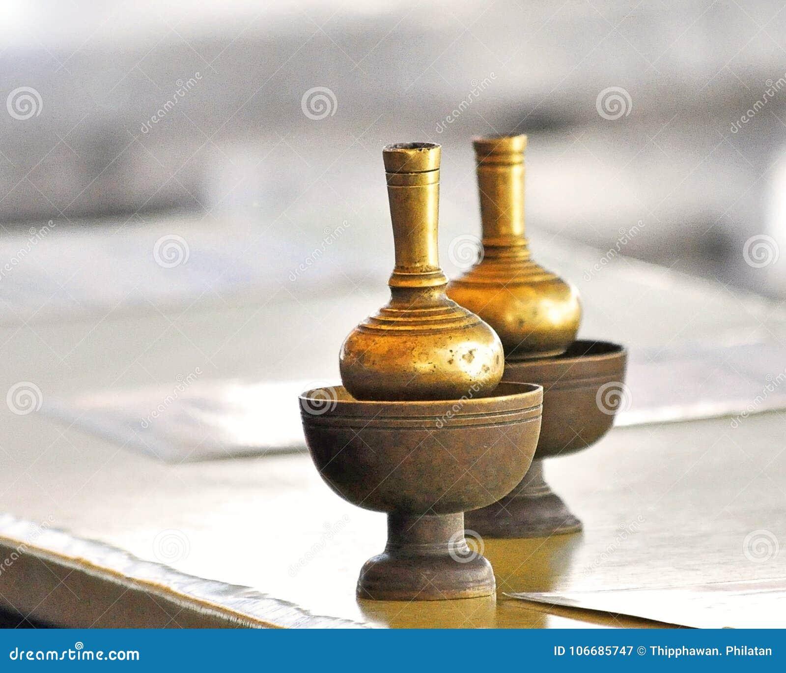 对填装的水的黄铜瓶子在泰国寺庙