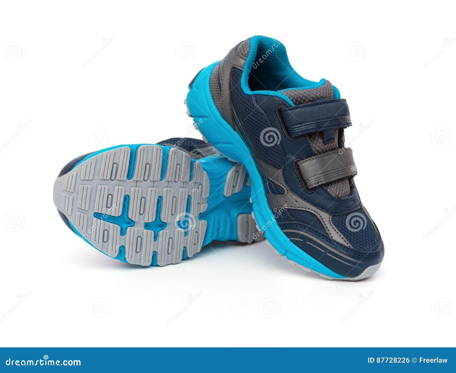 对孩子的蓝色和黑运动的鞋子在白色