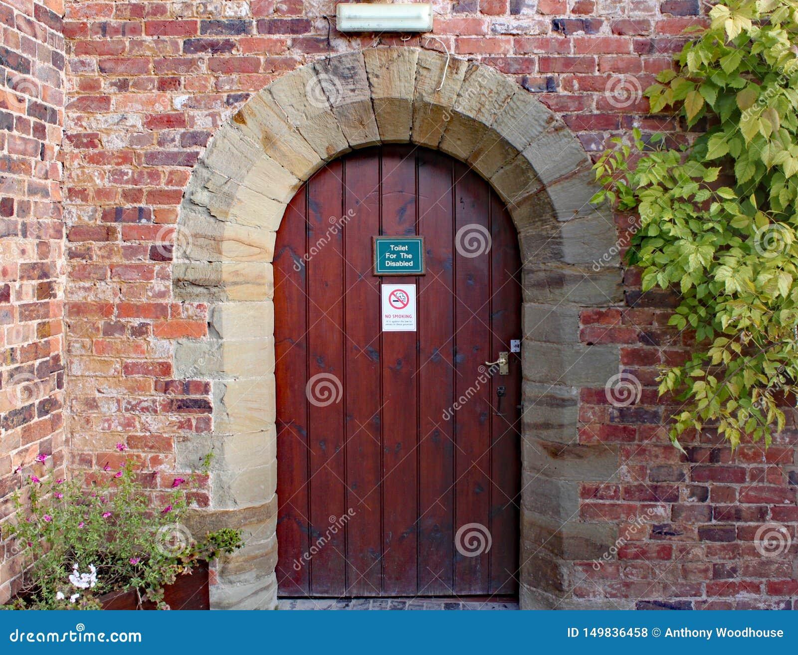对残疾洗手间的老木门在阿莱树木园在米德兰平原在英国