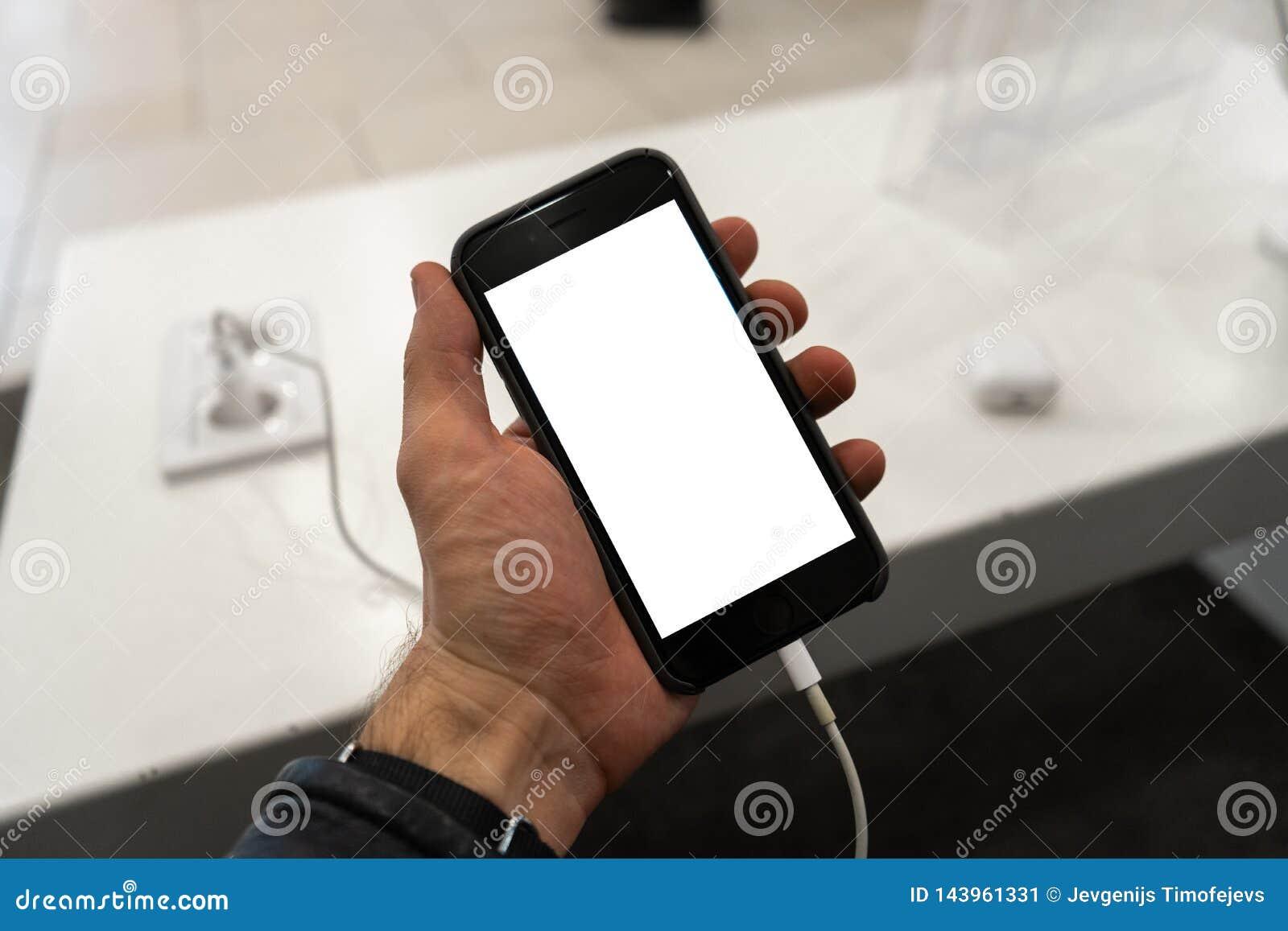 对电话的现实用途在举行与空您的广告和的文本的赠送阅本空间的人的手上-假装广告牌和