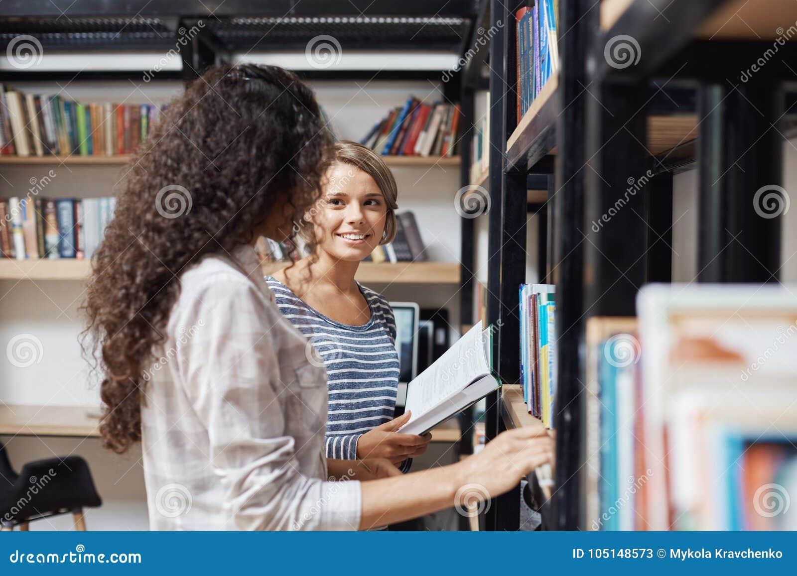 对站立近的书架的偶然时髦的衣裳的年轻美丽的女孩在图书馆里,看彼此