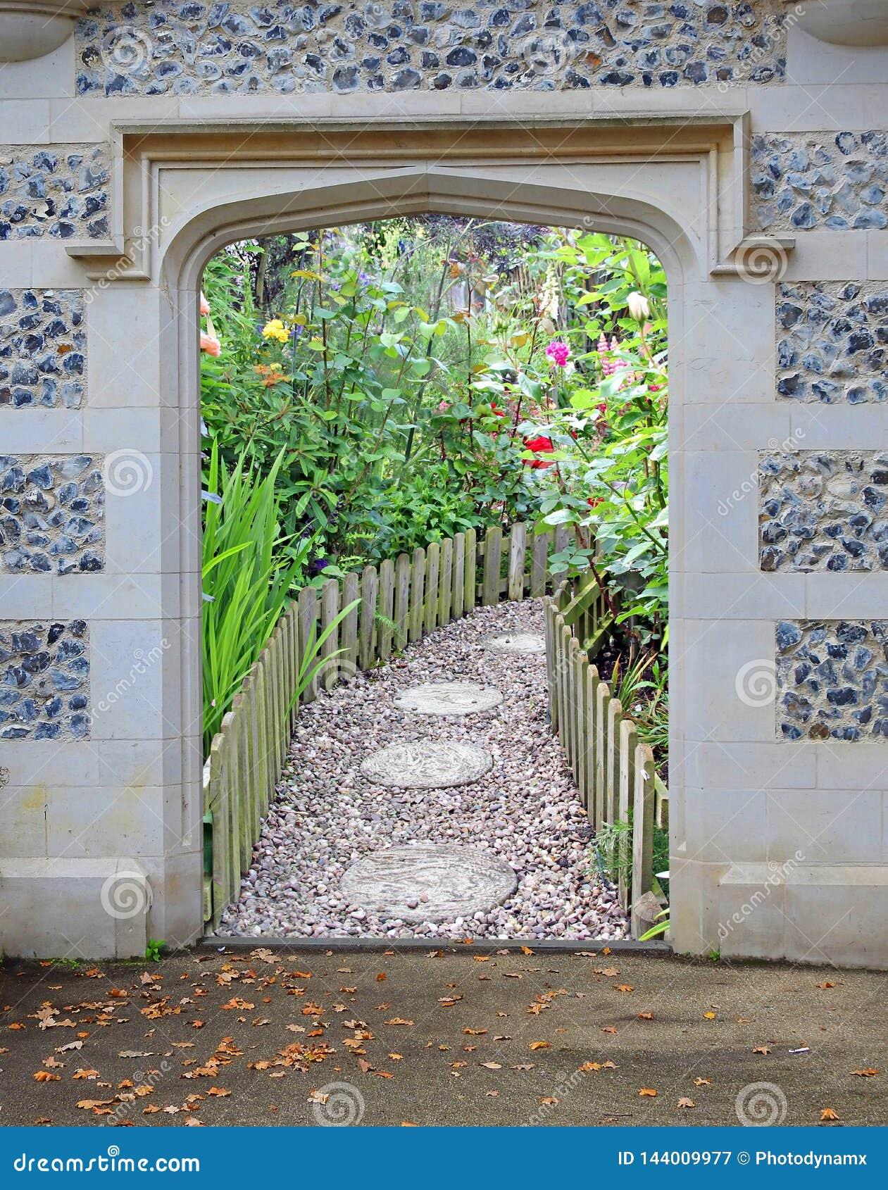 对美丽的庭院花植物的石曲拱门户门入口