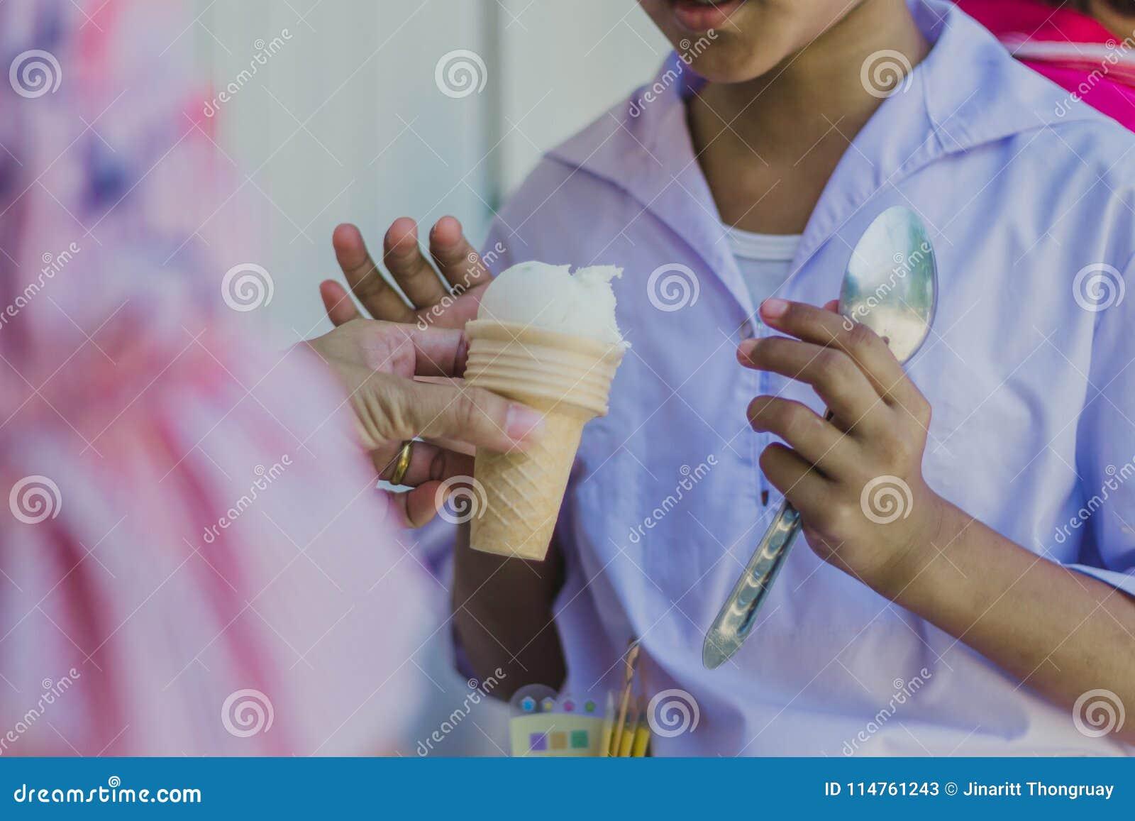 对老师` s手的特写镜头给冰淇凌学生
