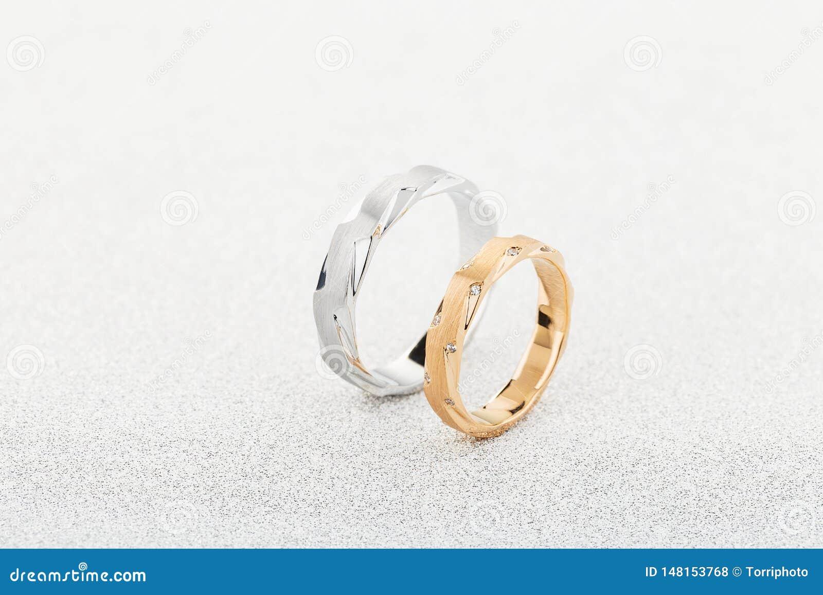 对银色人的圆环和桃红色金妇女的圆环与金刚石在白色闪烁背景