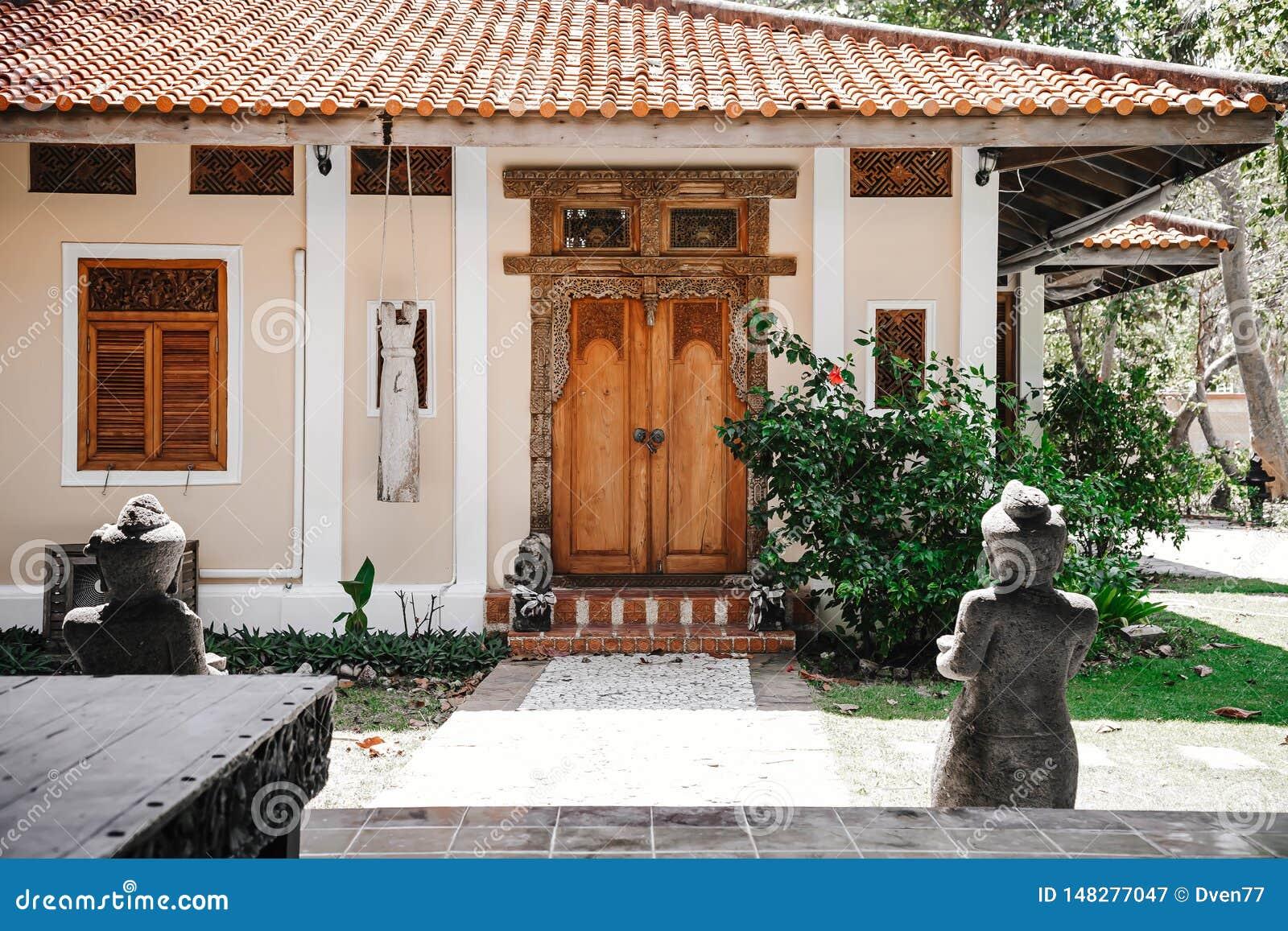 对黄色房子的入口 与被雕刻的样式的老木门 导致一个锁着的门的石道路