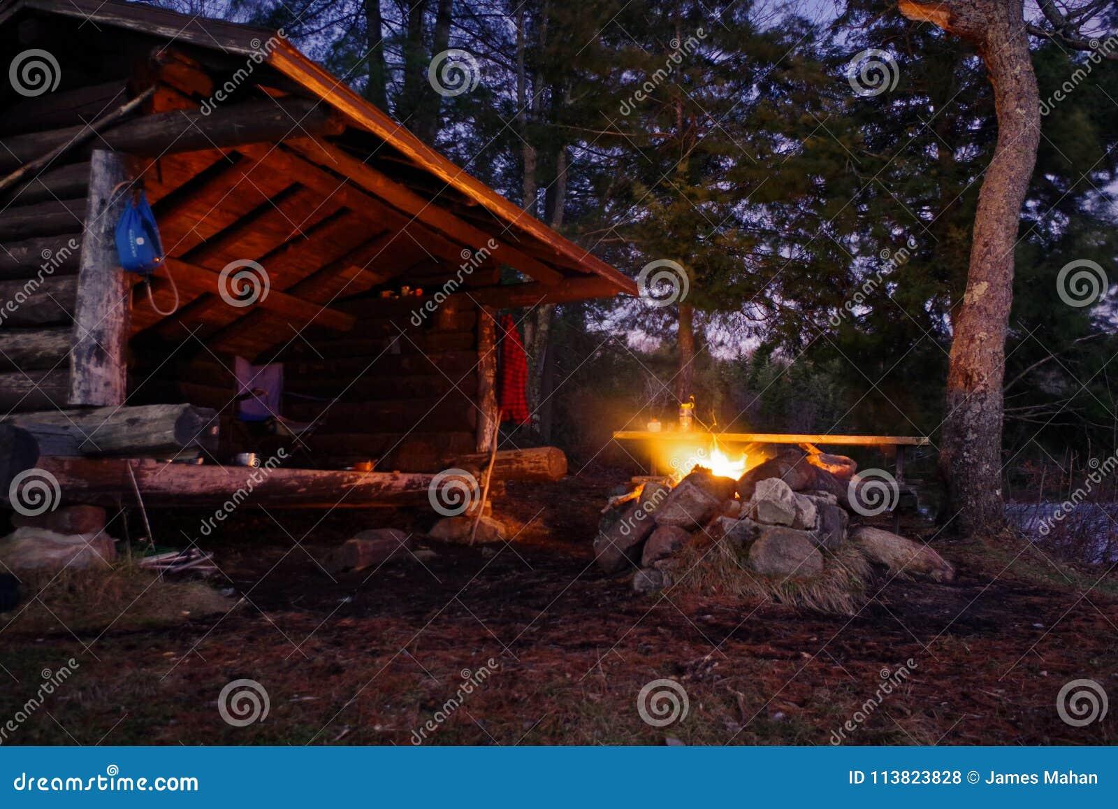 对Bushcraft阵营风雨棚的阿迪朗达克倾斜与火在山的晚上
