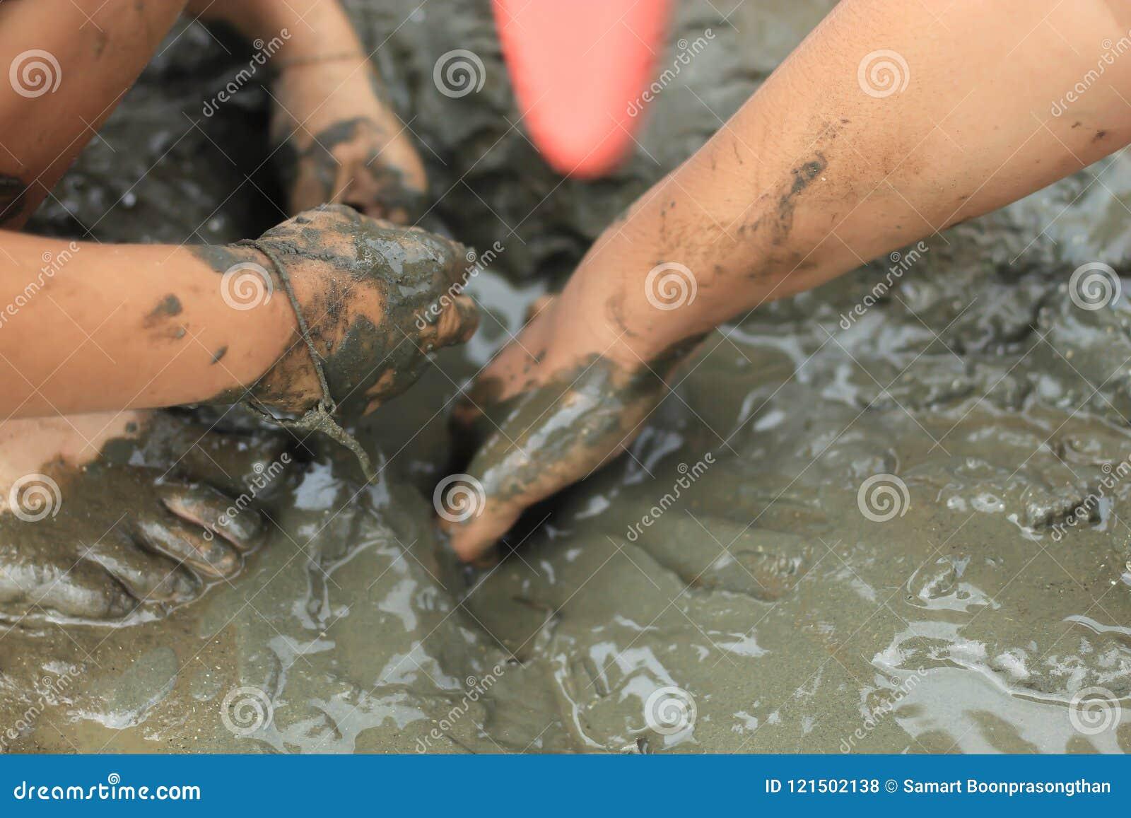 寻找在海底泥的男孩蜗牛壳