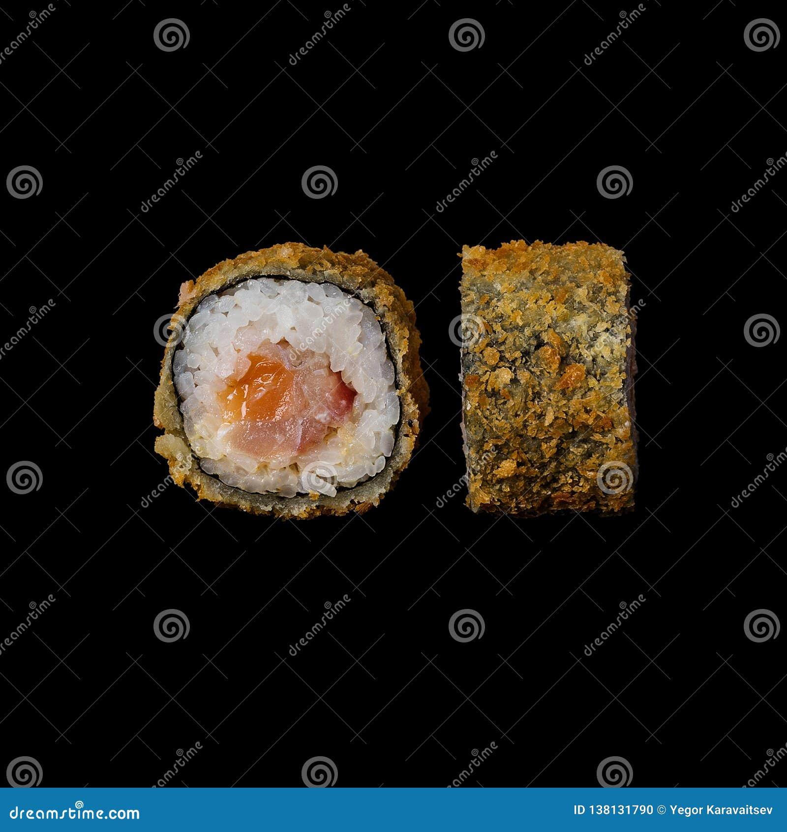 寿司 与三文鱼天麸罗和奶油奶酪的卷,隔绝在黑背景中