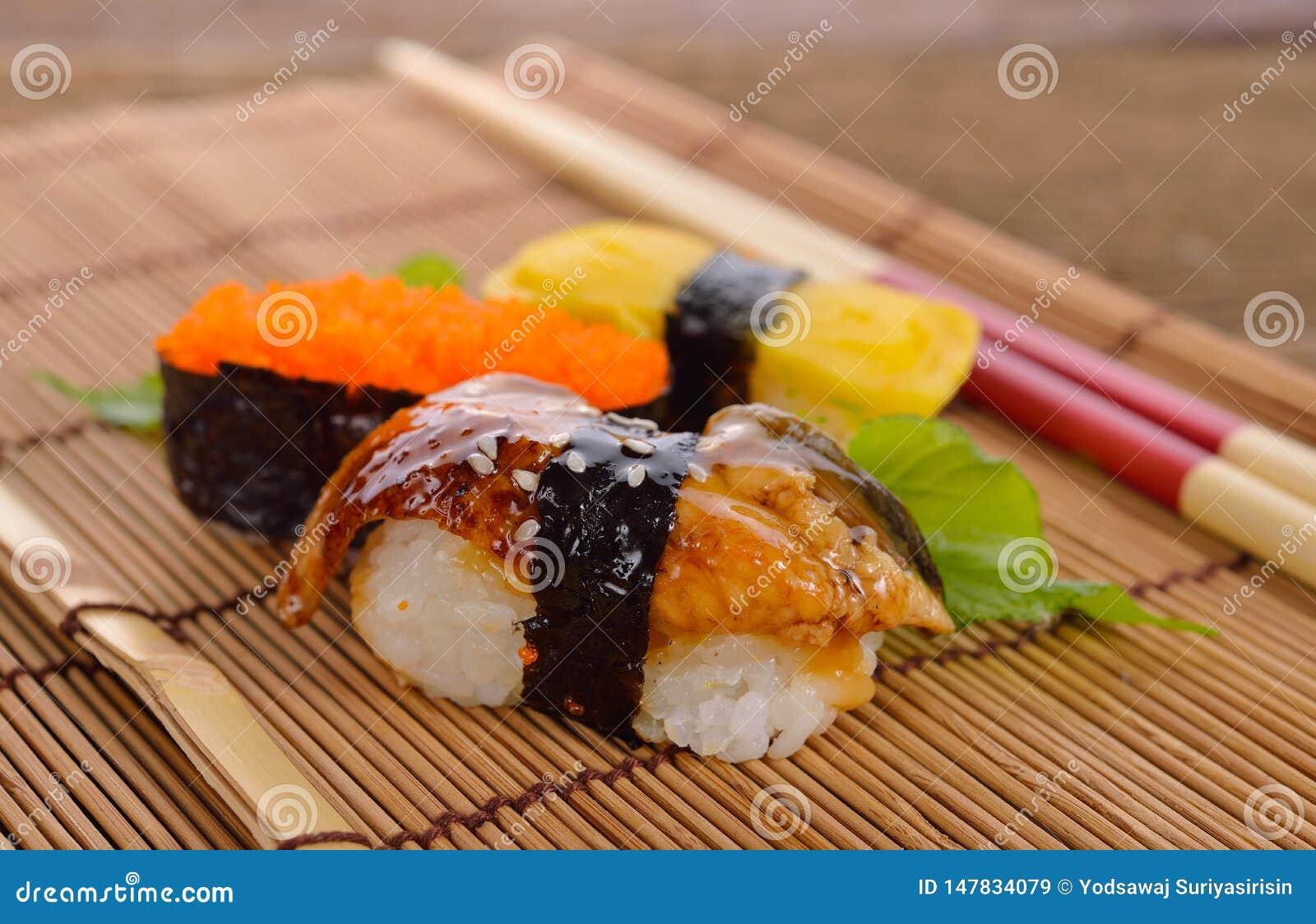 寿司nigiri和生鱼片在有筷子的竹席子服务在木背景