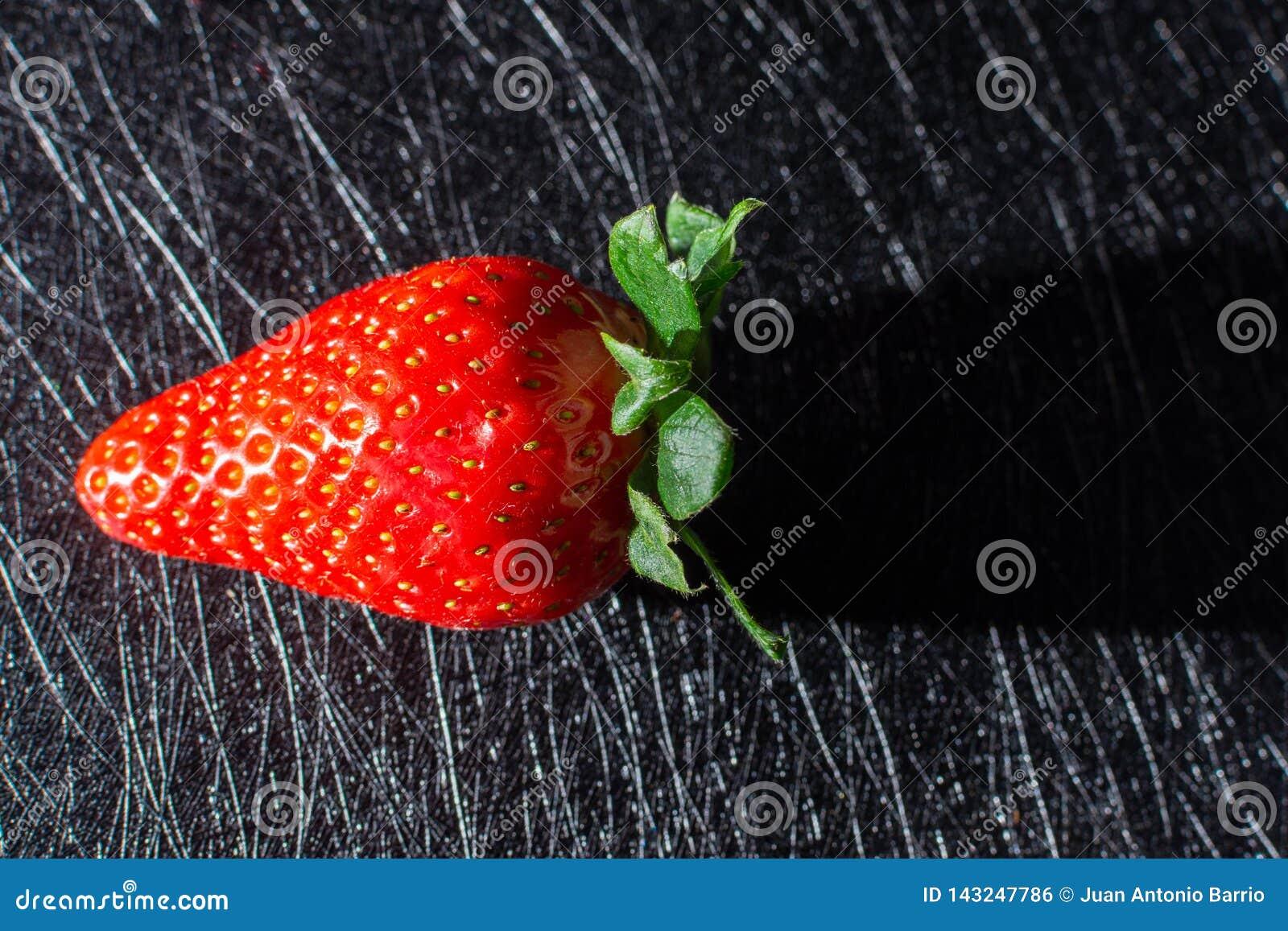 射出它的阴影的草莓隔绝在与黑纹理的背景中