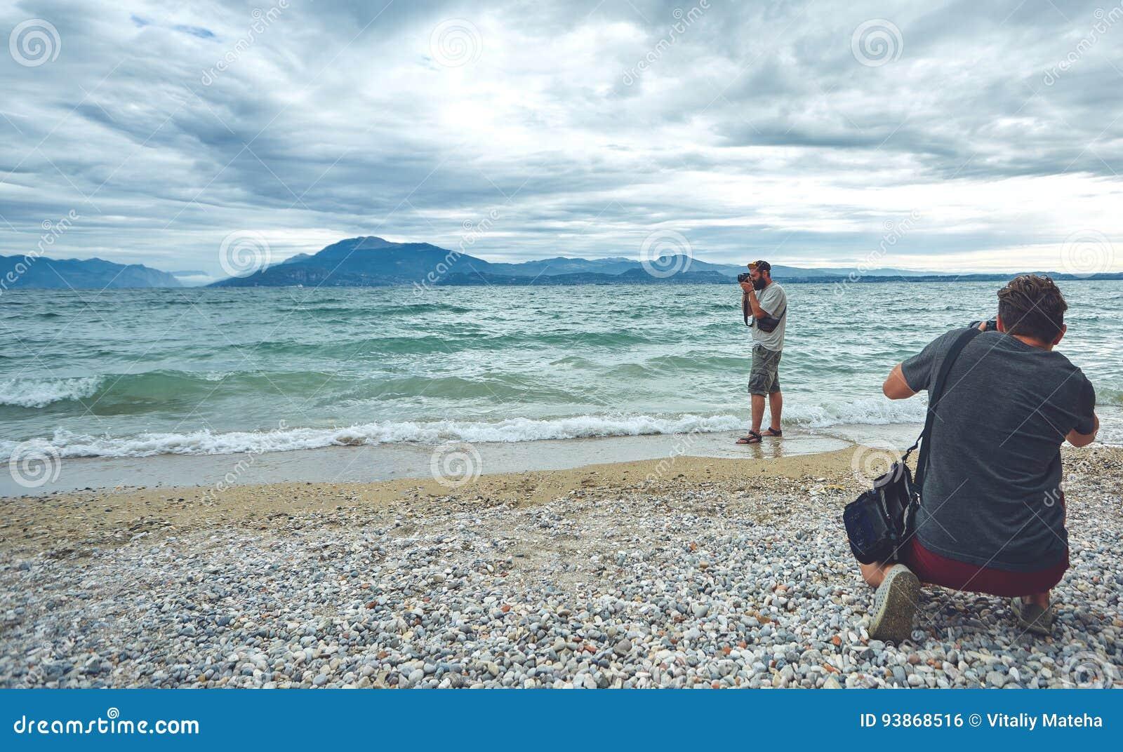 射击在海的摄影师靠岸多云天