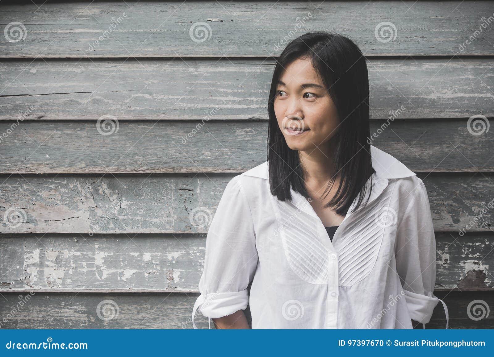 射击照片亚洲妇女画象穿戴白色衬衣和看斜向一边有木墙壁背景
