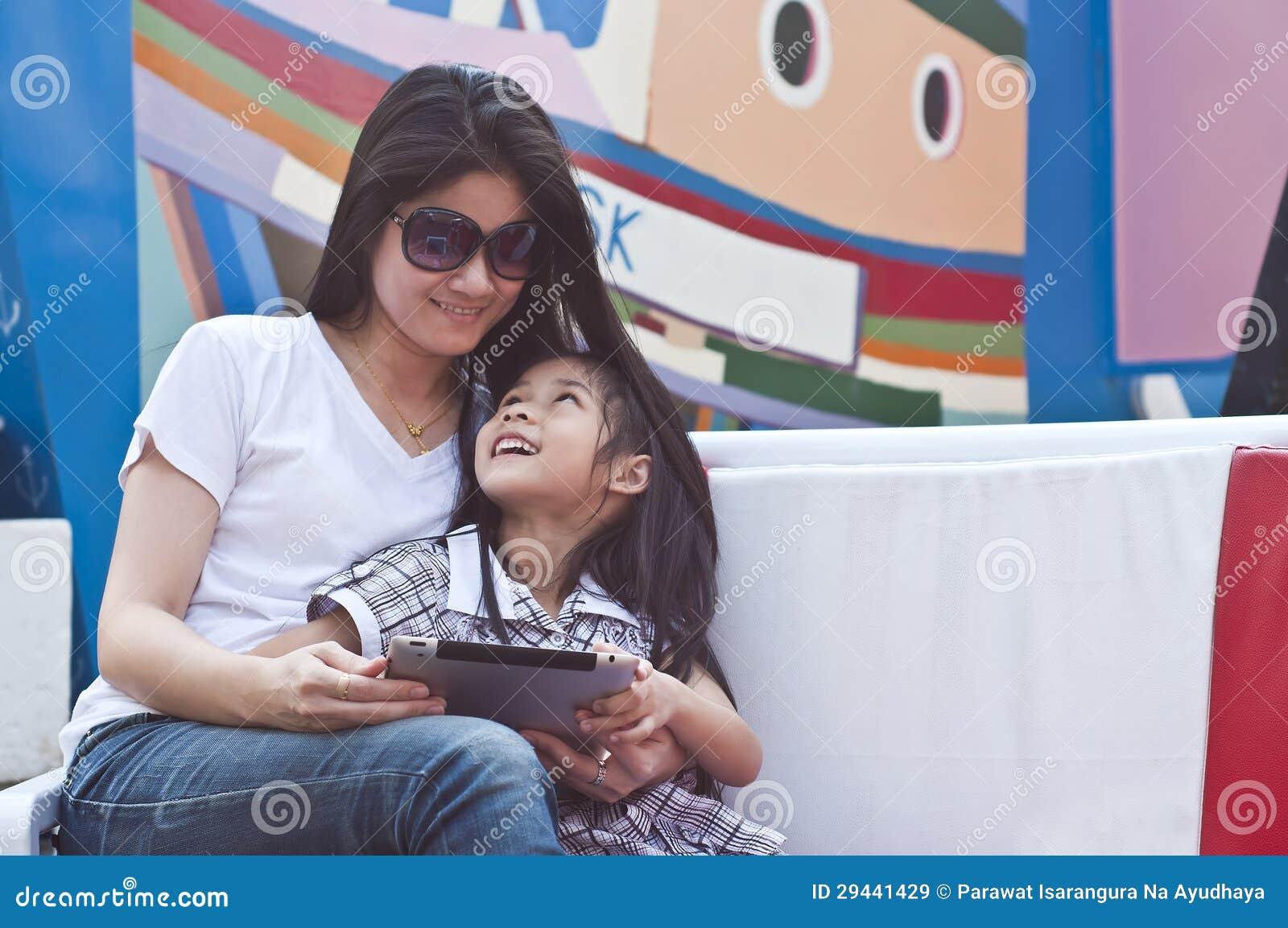 小亚裔女孩和妈妈享用片剂个人计算机。