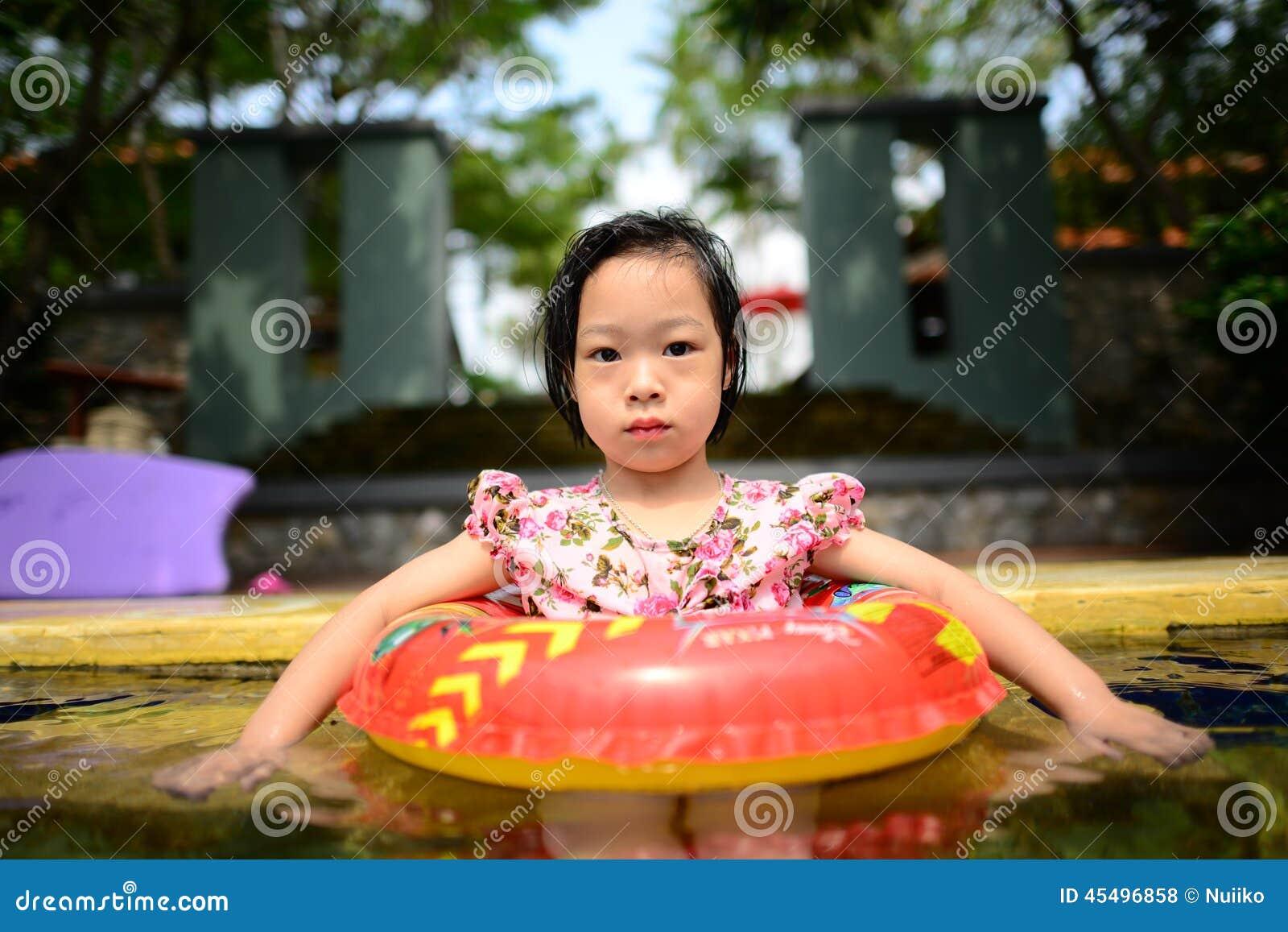 小亚裔女孩在水池游泳