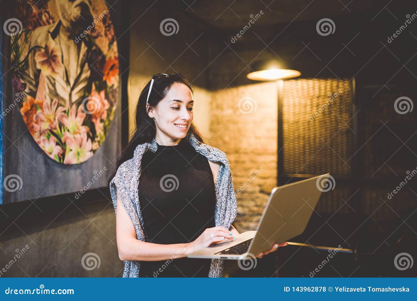 小企业和技术的概念 黑礼服和灰色毛线衣立场的年轻美丽的深色的女实业家