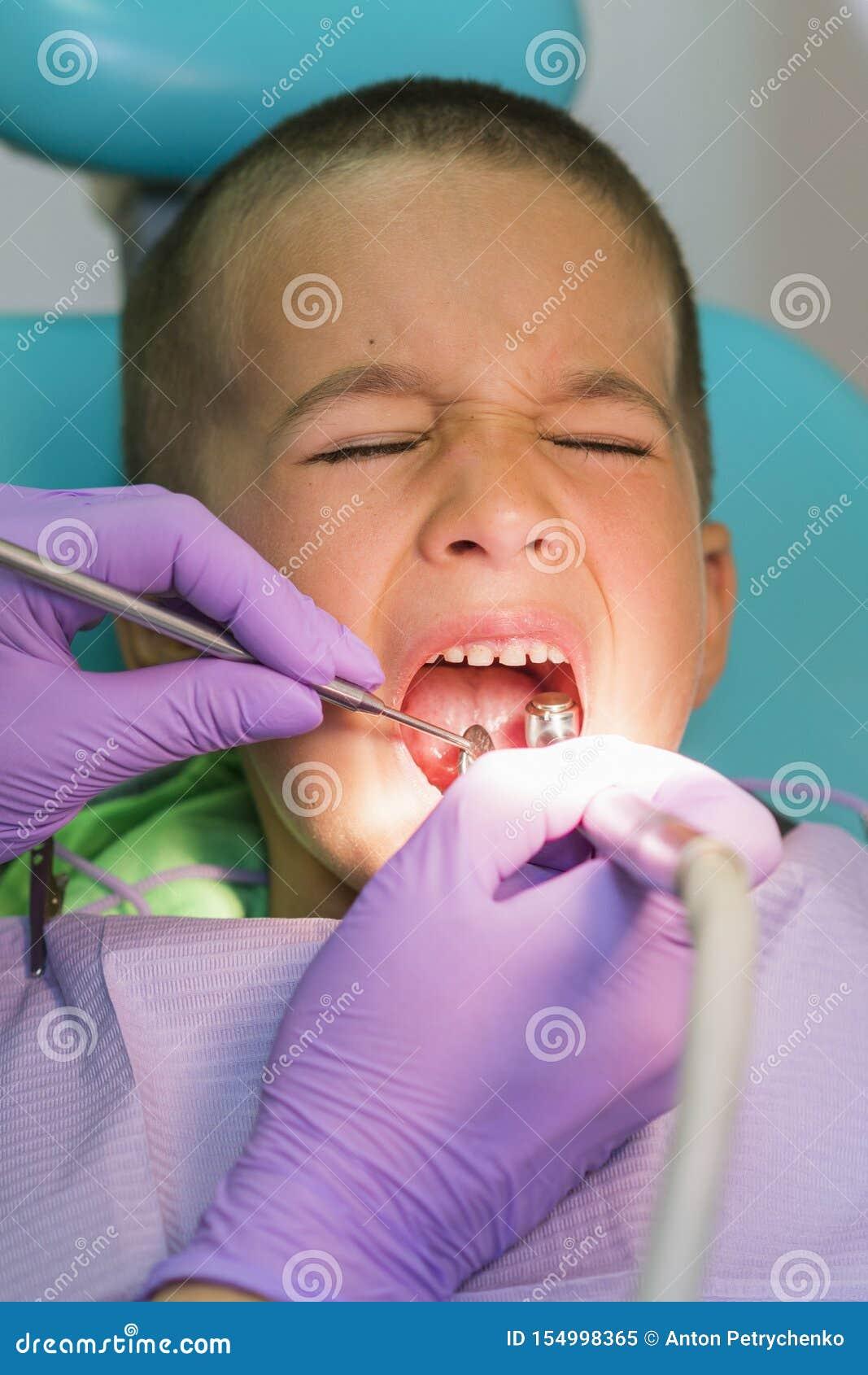 小儿科牙医审查在牙医椅子的小男孩牙在牙齿诊所 有牙医的一个孩子