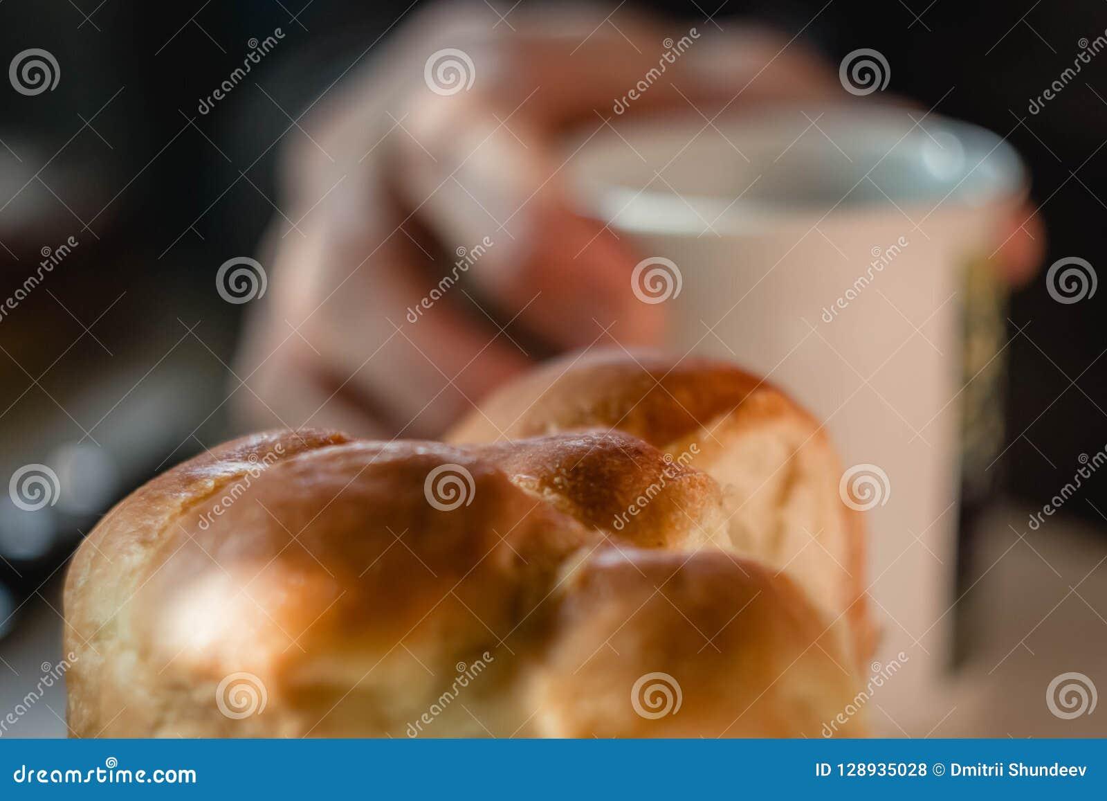 小圆面包和杯子在白色木桌上的果子茶 供以人员做茶的手,慢慢地搅动与匙子 可口养育的早餐