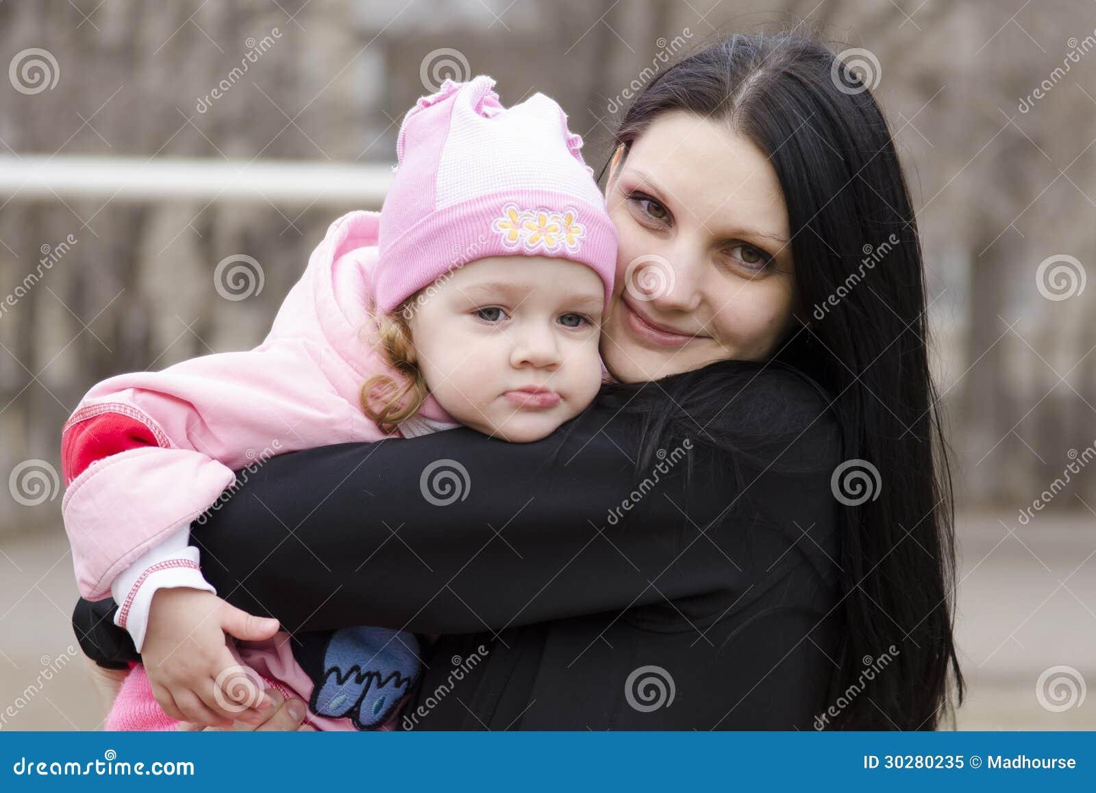 小女孩在我的母亲肩膀周道地说谎