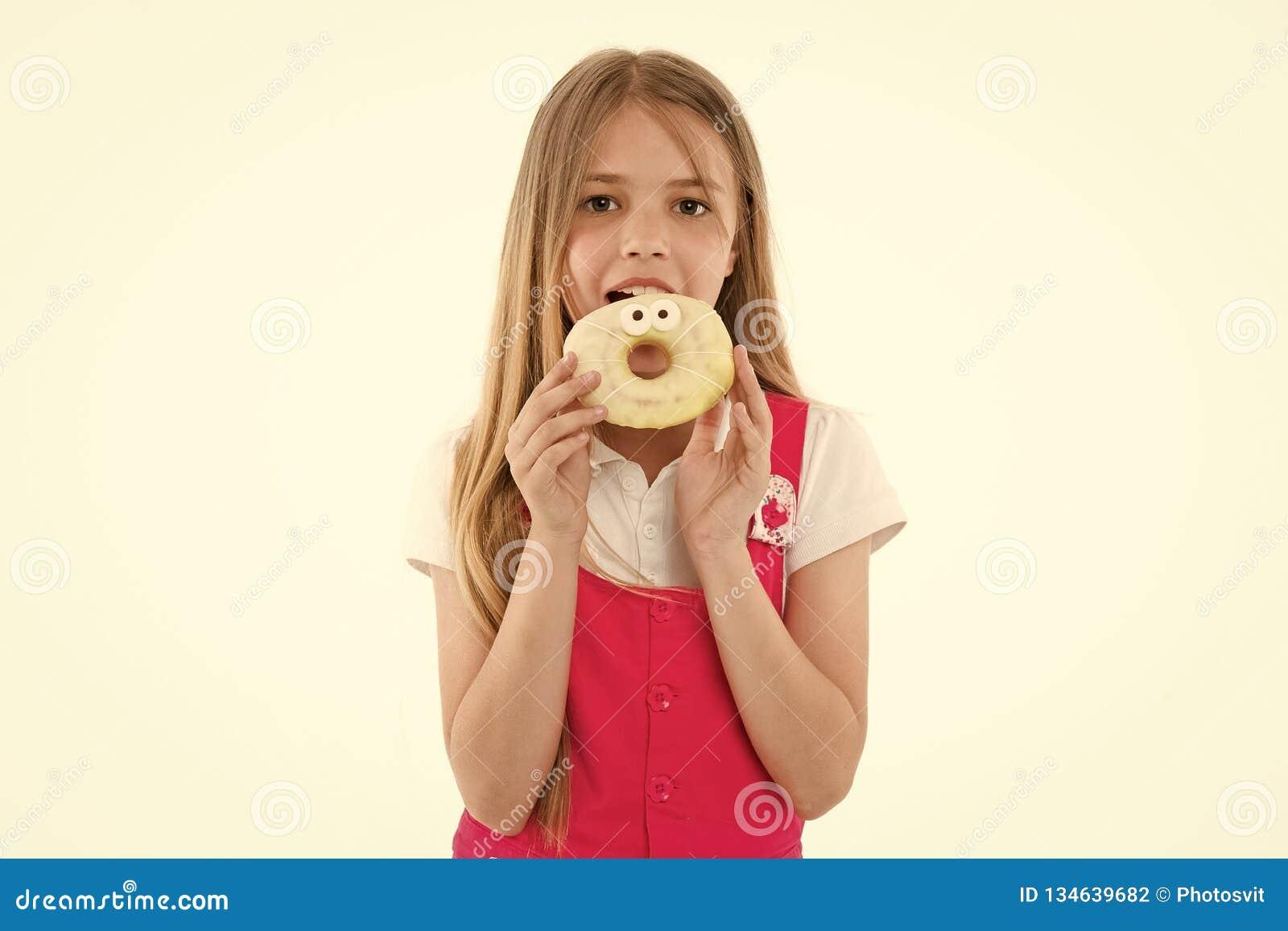 小女孩吃在白色隔绝的多福饼 孩子用给上釉的圆环多福饼 孩子用速食 快餐和点心的食物