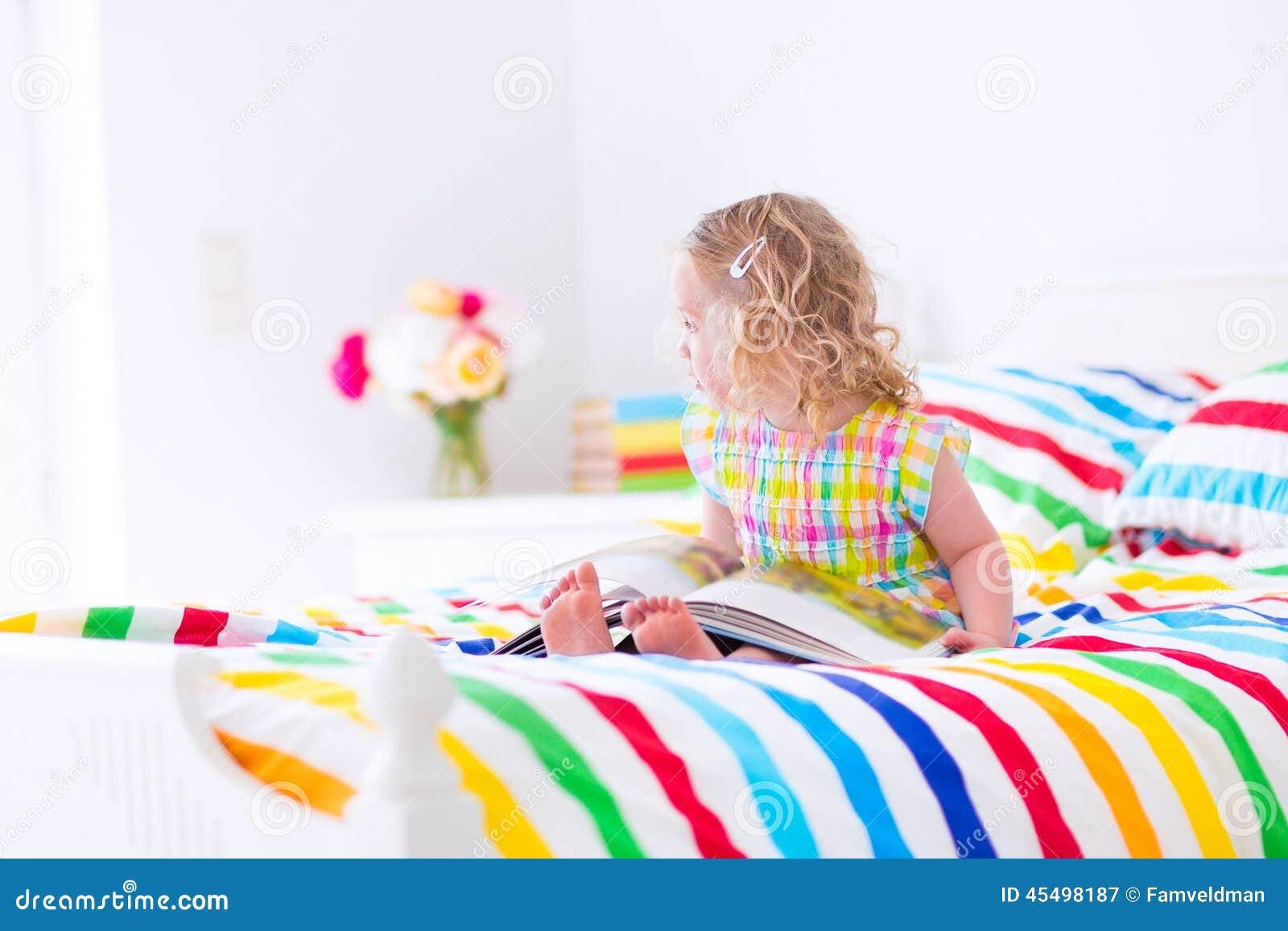 小女孩在床上的读一本书