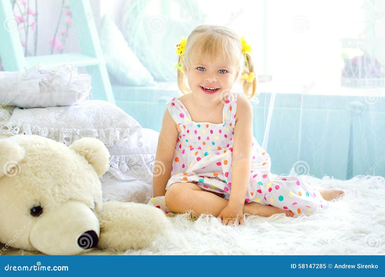 小女孩在有大白色玩具熊的轻的卧室