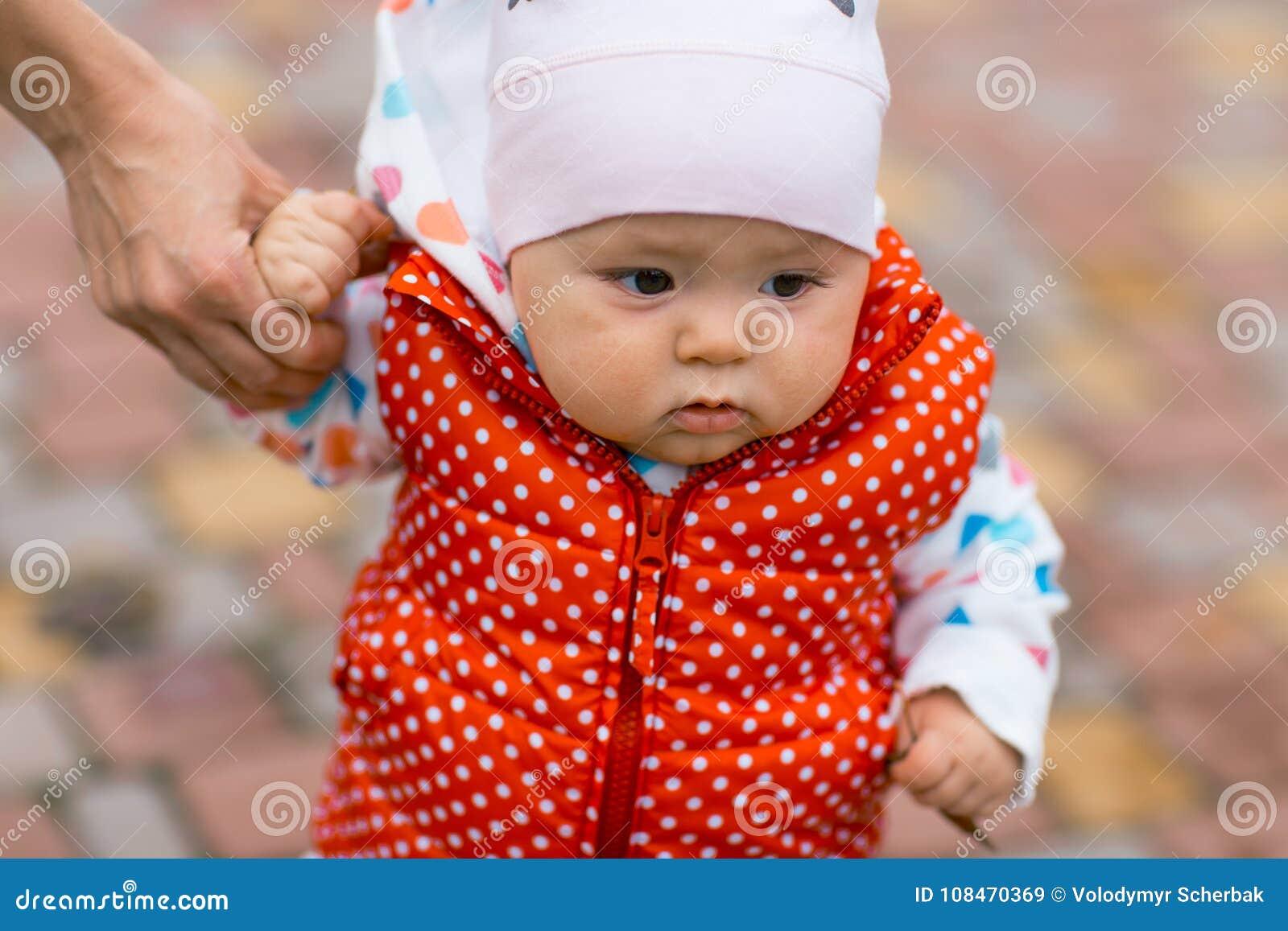 小女孩学会走,采取它的第一步 女性手母亲支持孩子