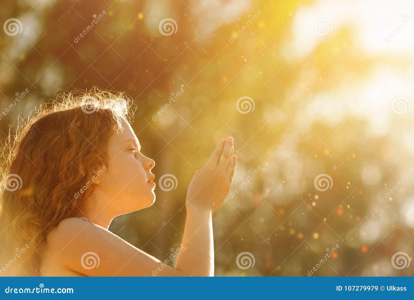 小女孩折叠了她手和祈祷