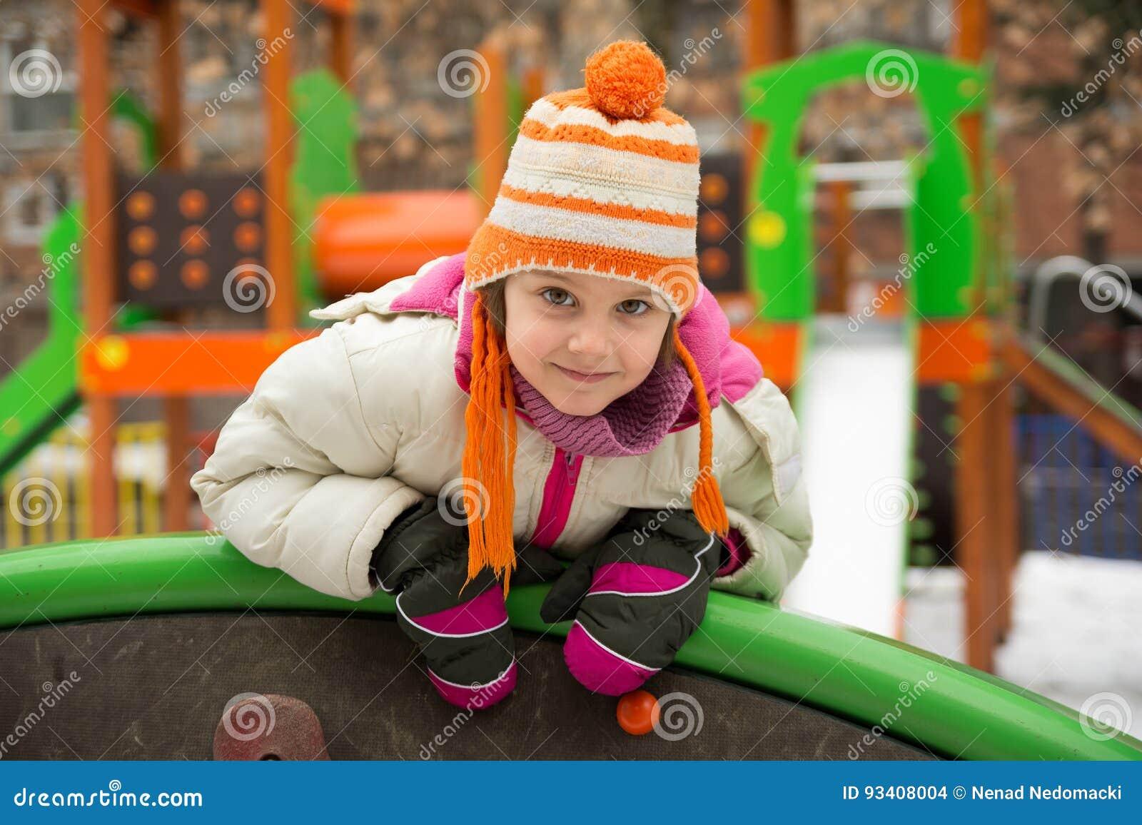 小女孩获得乐趣在冬天操场