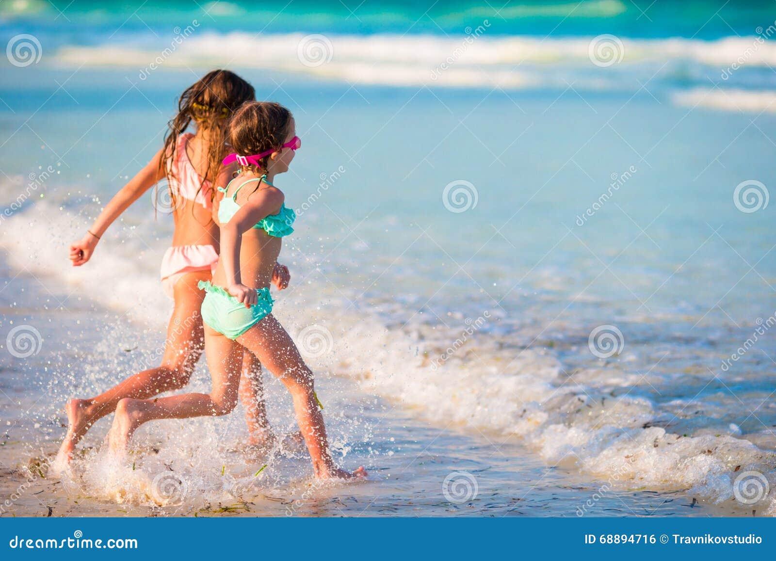 小女孩获得乐趣在热带海滩在一起使用在浅水区的暑假时