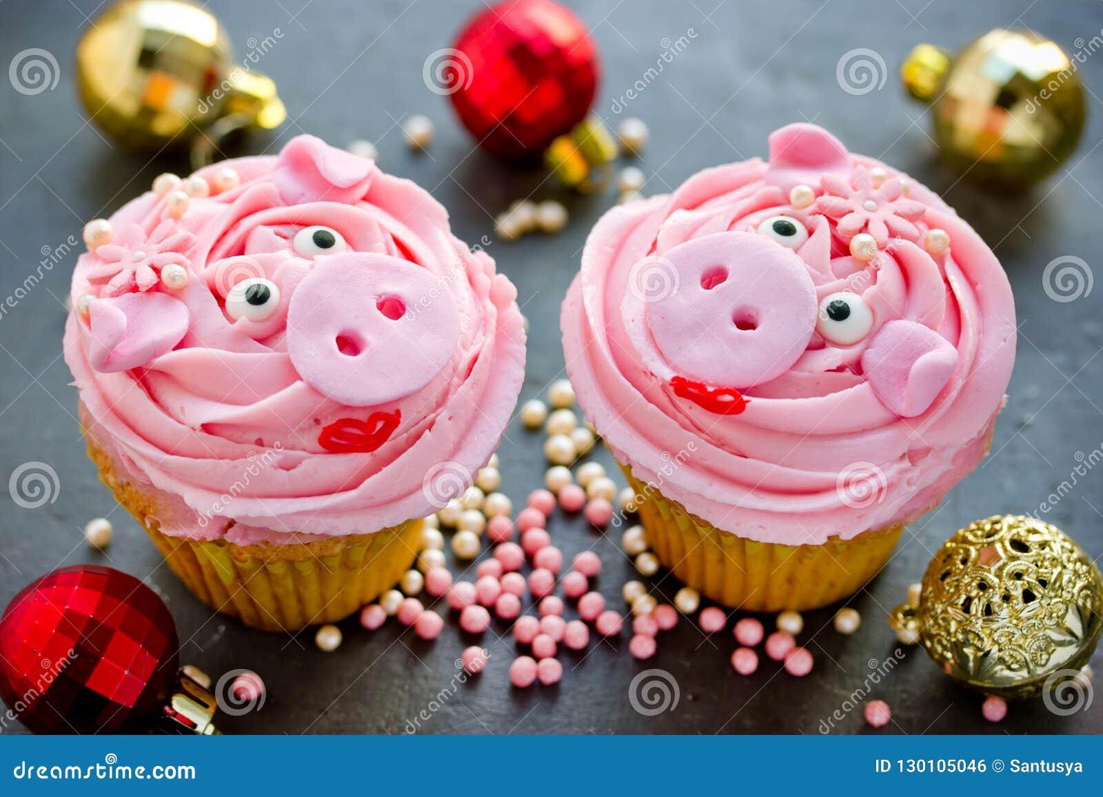 小姐贪心杯形蛋糕-美丽和用桃红色奶油装饰的可口蛋糕塑造了滑稽的贪心面孔