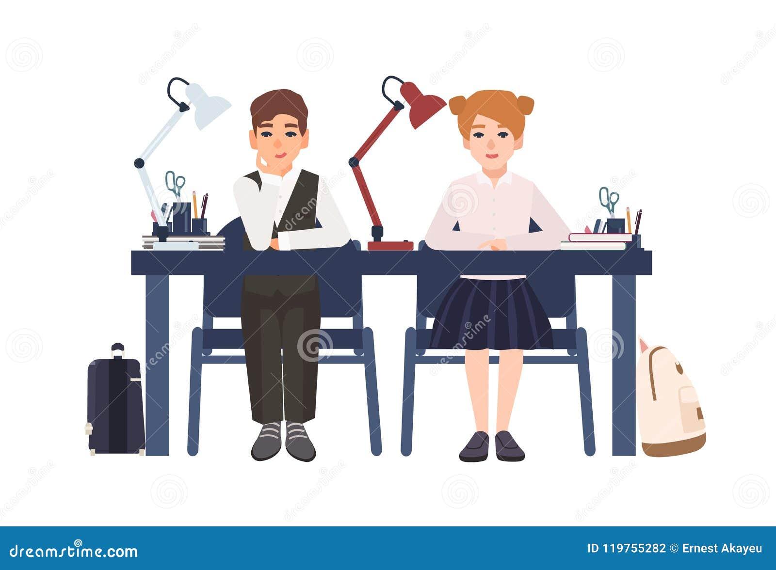 小学男孩和女孩制服的在书桌在被隔绝的教室坐白色背景 微笑的学生或