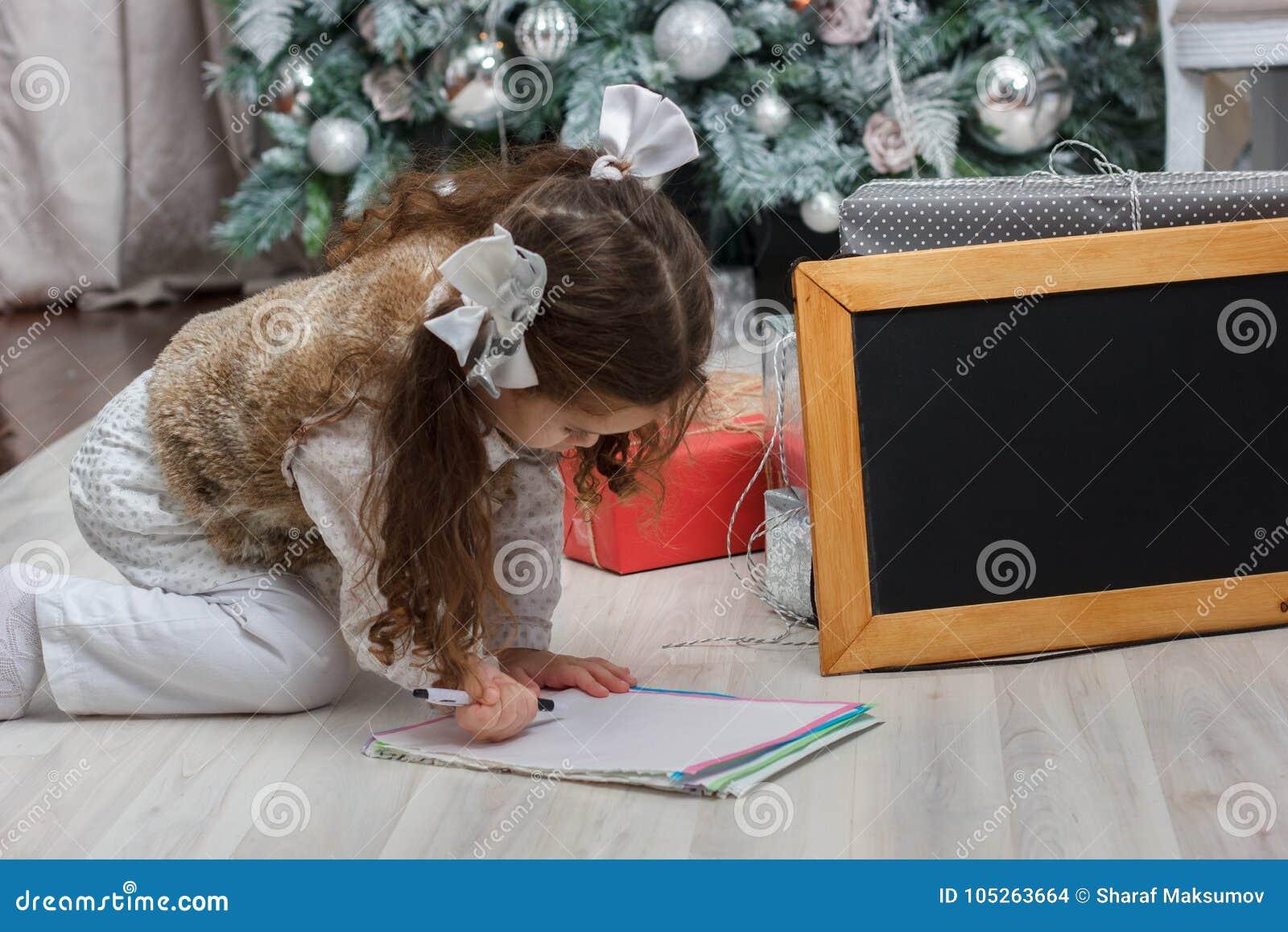 小孩女孩与愿望的文字信件对圣诞老人在圣诞节