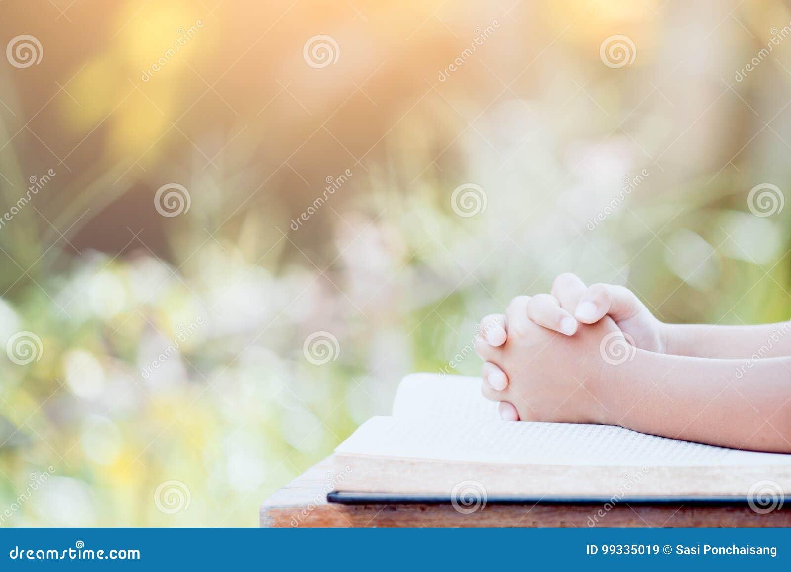 小孩女孩手在圣经的祷告折叠了