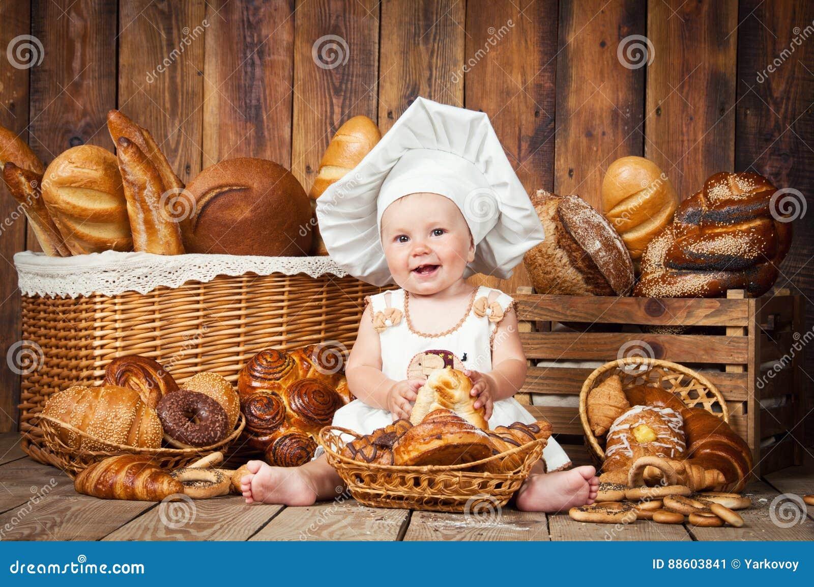 小孩子在篮子背景中烹调一个新月形面包与卷和面包的