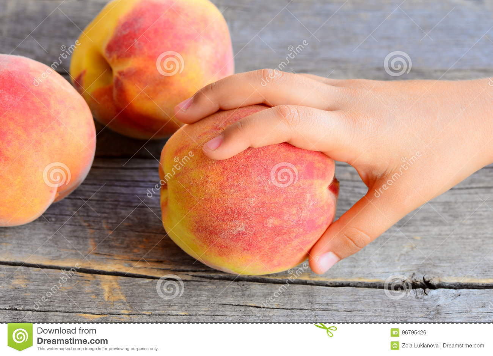 小孩子采取一个成熟桃子 在葡萄酒木桌上的甜新鲜的桃子 孩子的可口和健康食物在夏天