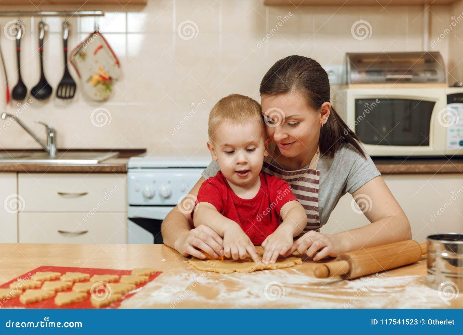 小孩男孩帮助母亲烹调姜饼干 愉快的家庭妈妈和孩子在周末早晨在家 关系