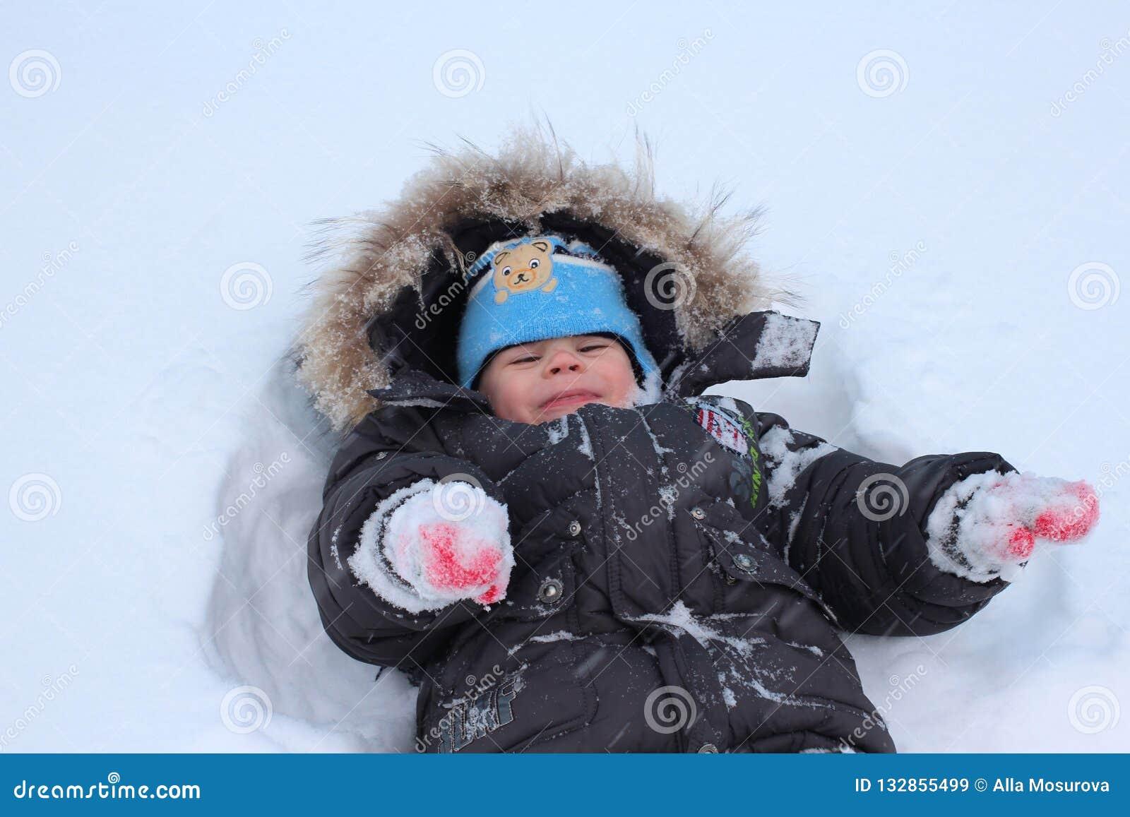 小孩笑的冬天在获得的雪下跌乐趣
