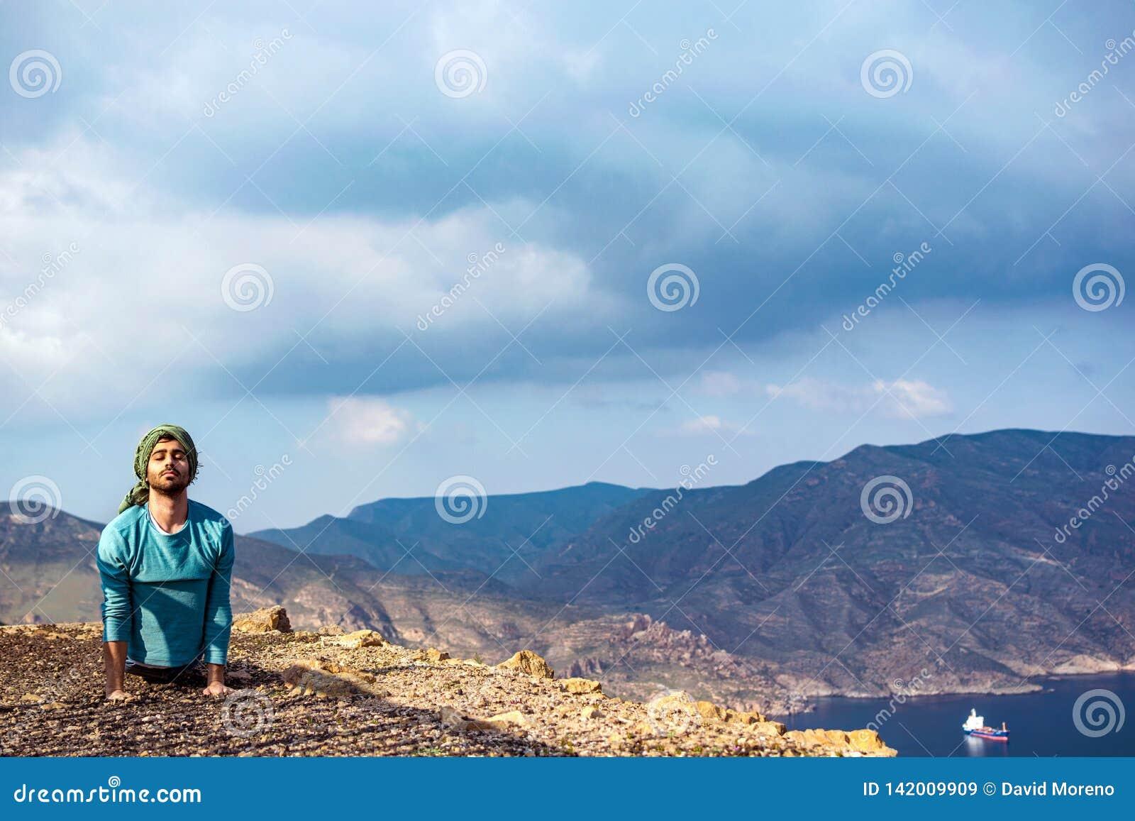 小山上缘执行瑜伽的峭壁岩石的年轻印度人