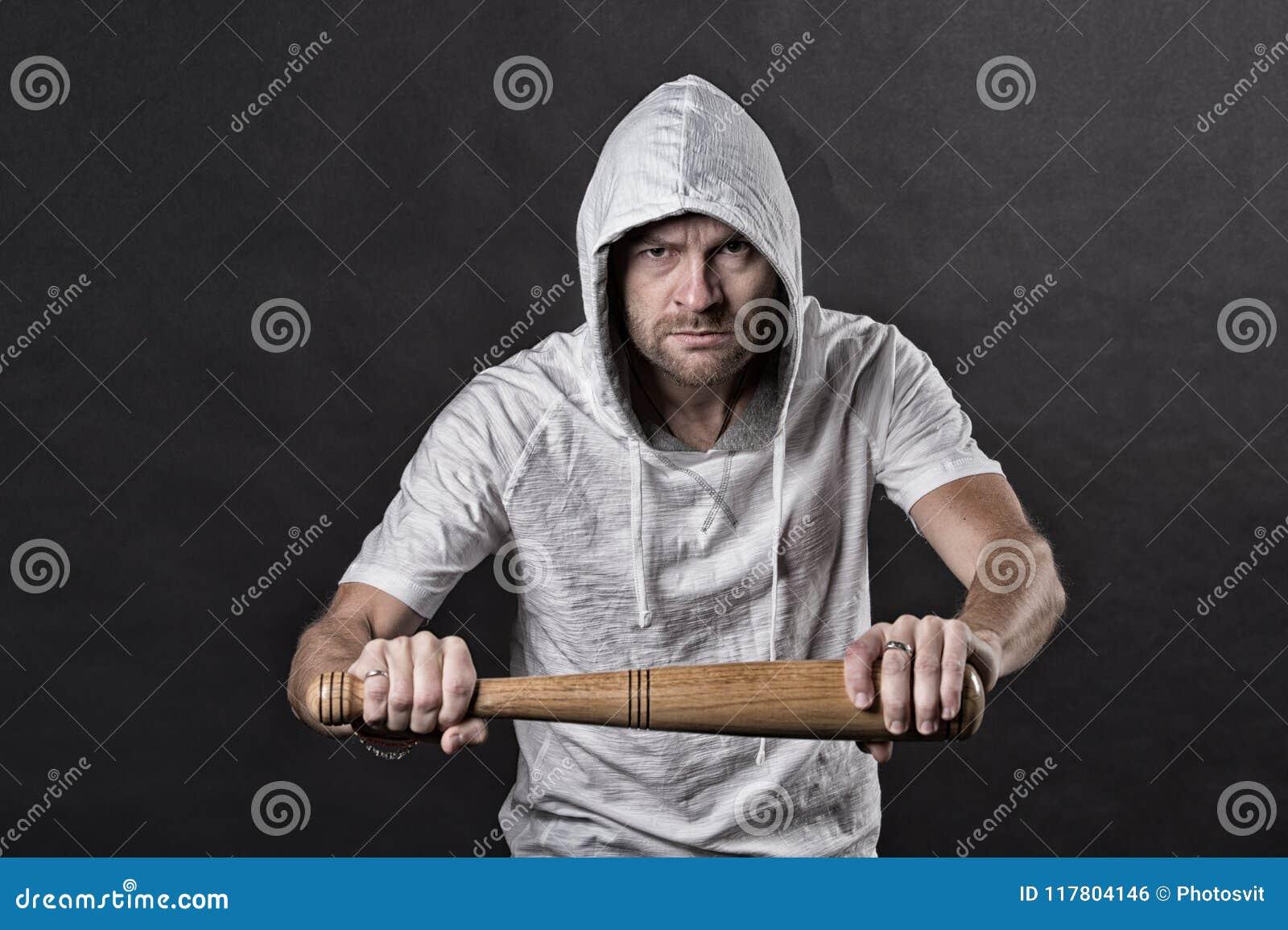 小流氓举行棒球棒 在有冠乌鸦T恤杉的有胡子的男服敞篷 匪徒人威胁与棒武器 侵略或