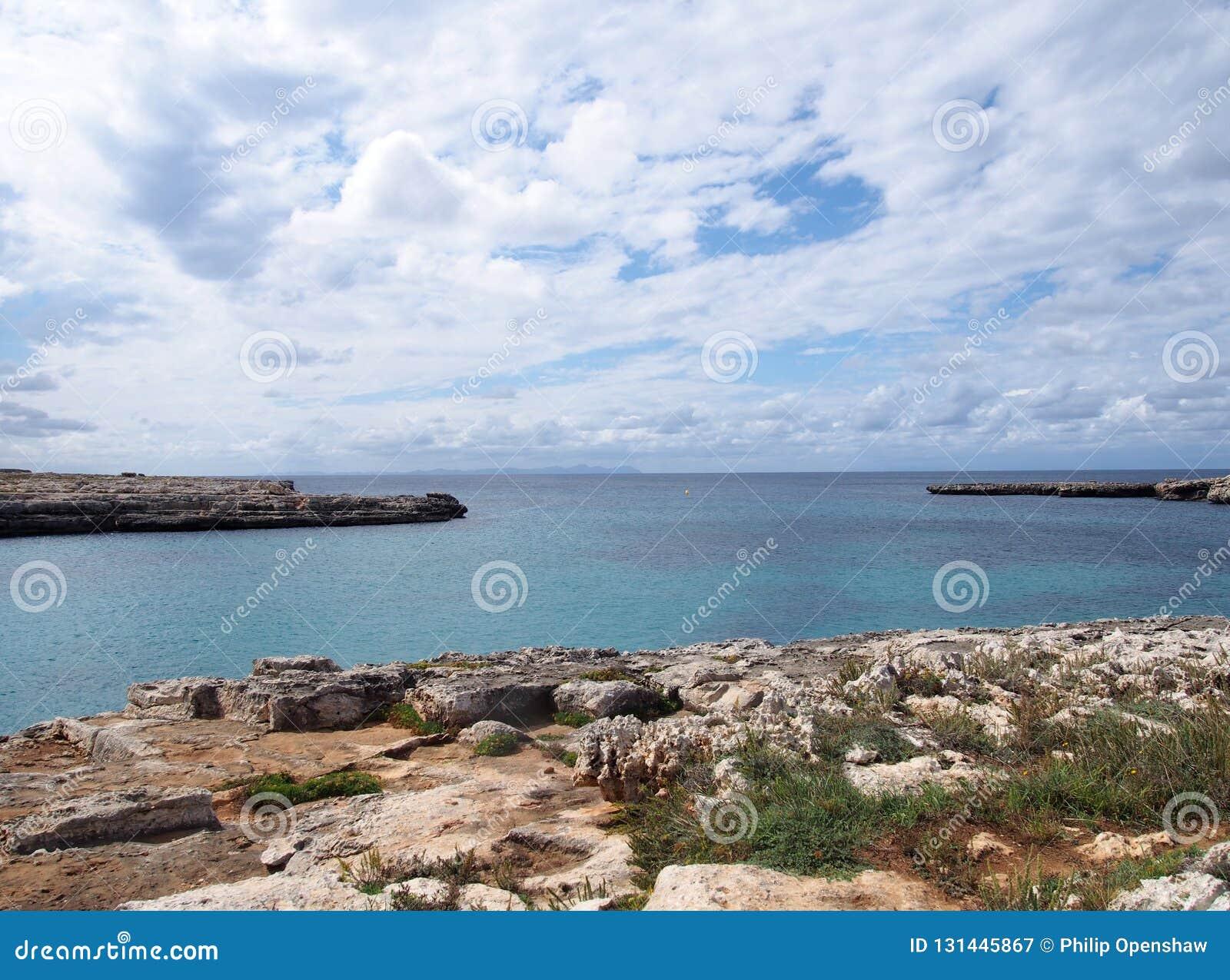 小海湾的Clifftop视图在cale santandria的在与岩石岸的menorca和有白色云彩的蓝色夏天海