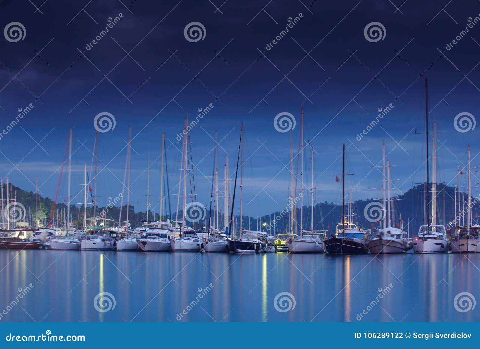 小游艇船坞在与被停泊的游艇的晚上