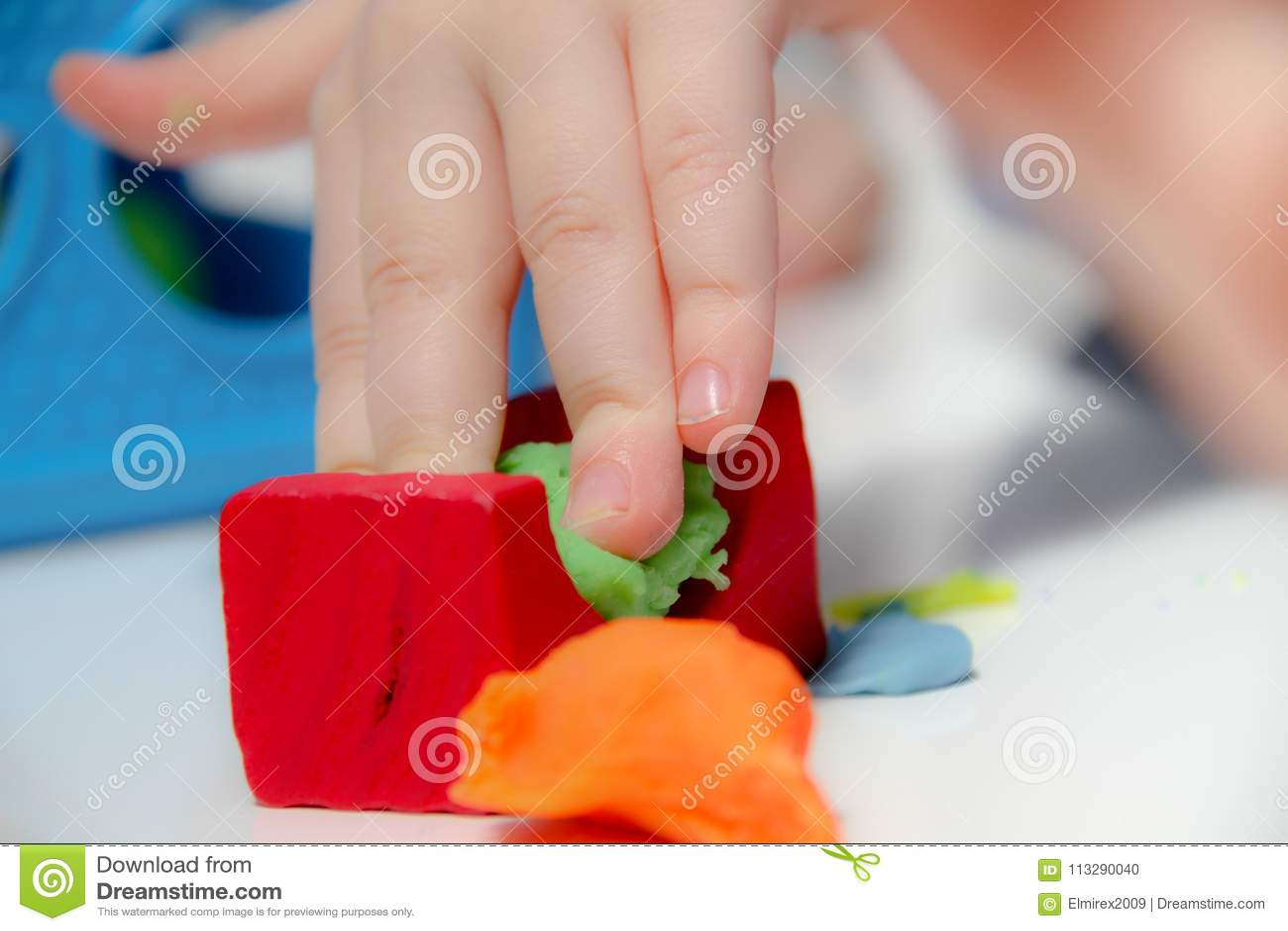 小男孩三岁坐桌和戏剧与彩色塑泥和木和塑料玩具、立方体和模子