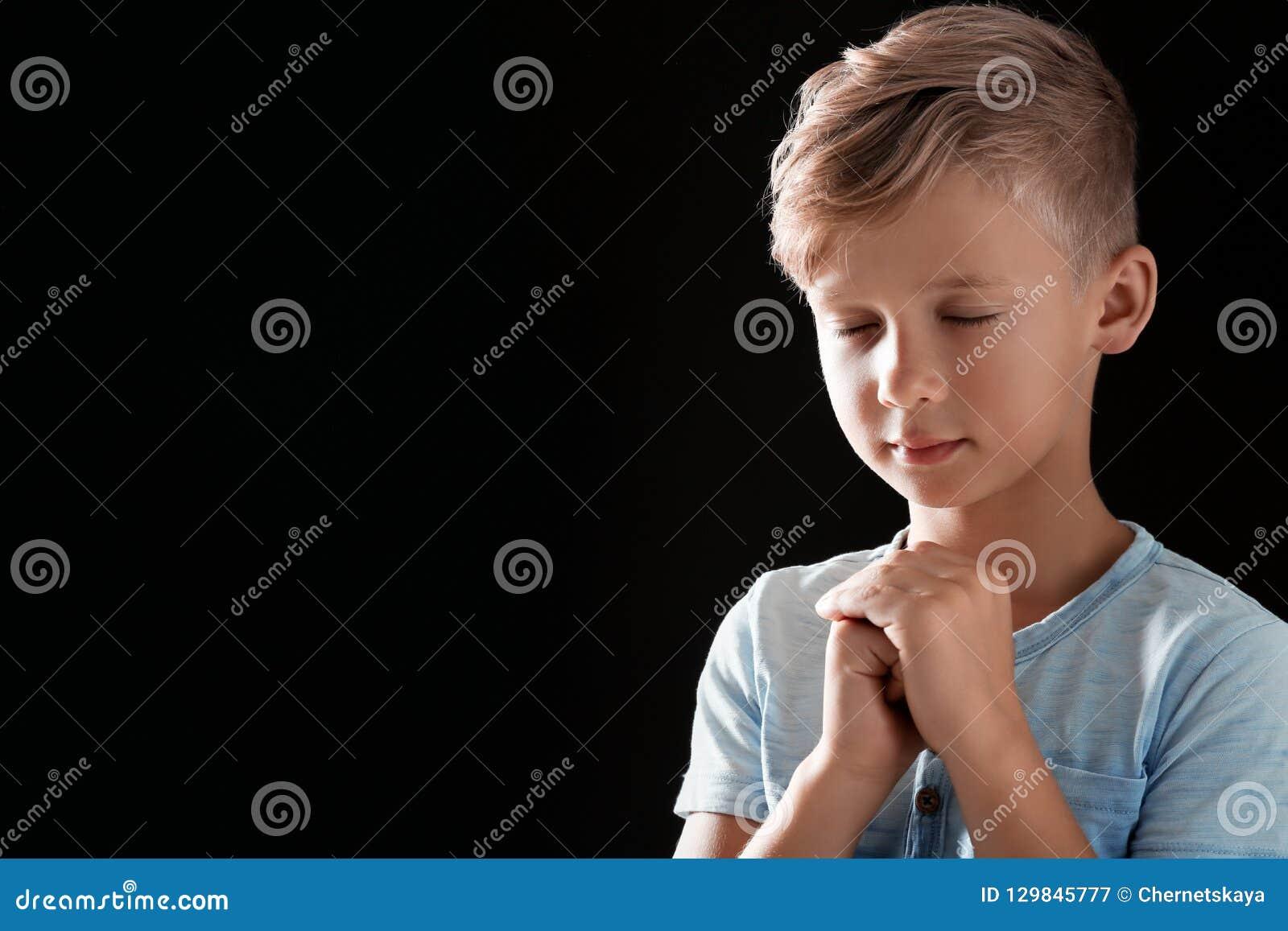 小男孩用为在黑背景的祷告一起扣紧的手