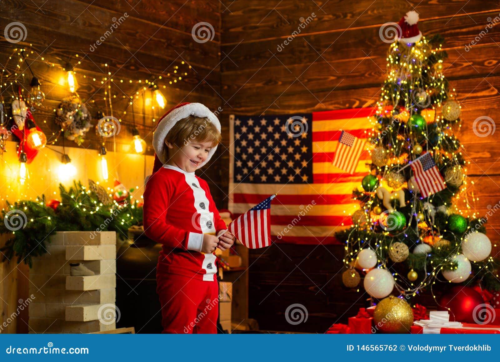 小男孩获得圣诞老人的帽子和的服装乐趣 美国传统概念 小孩庆祝圣诞节 真实的美国人
