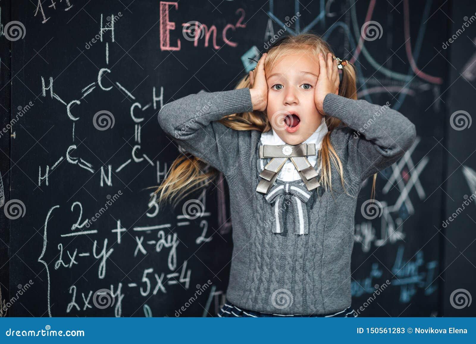 小白肤金发的女孩画象,抓住她的头 有学校惯例的黑板在背景,概念照片
