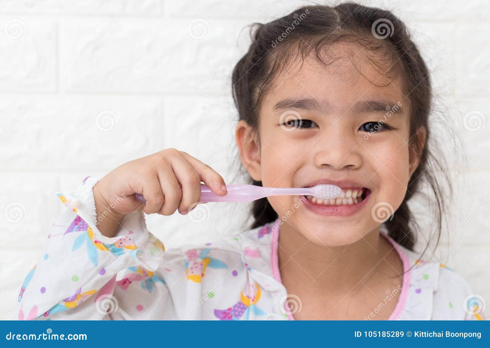 小的亚洲逗人喜爱的女孩刷子牙