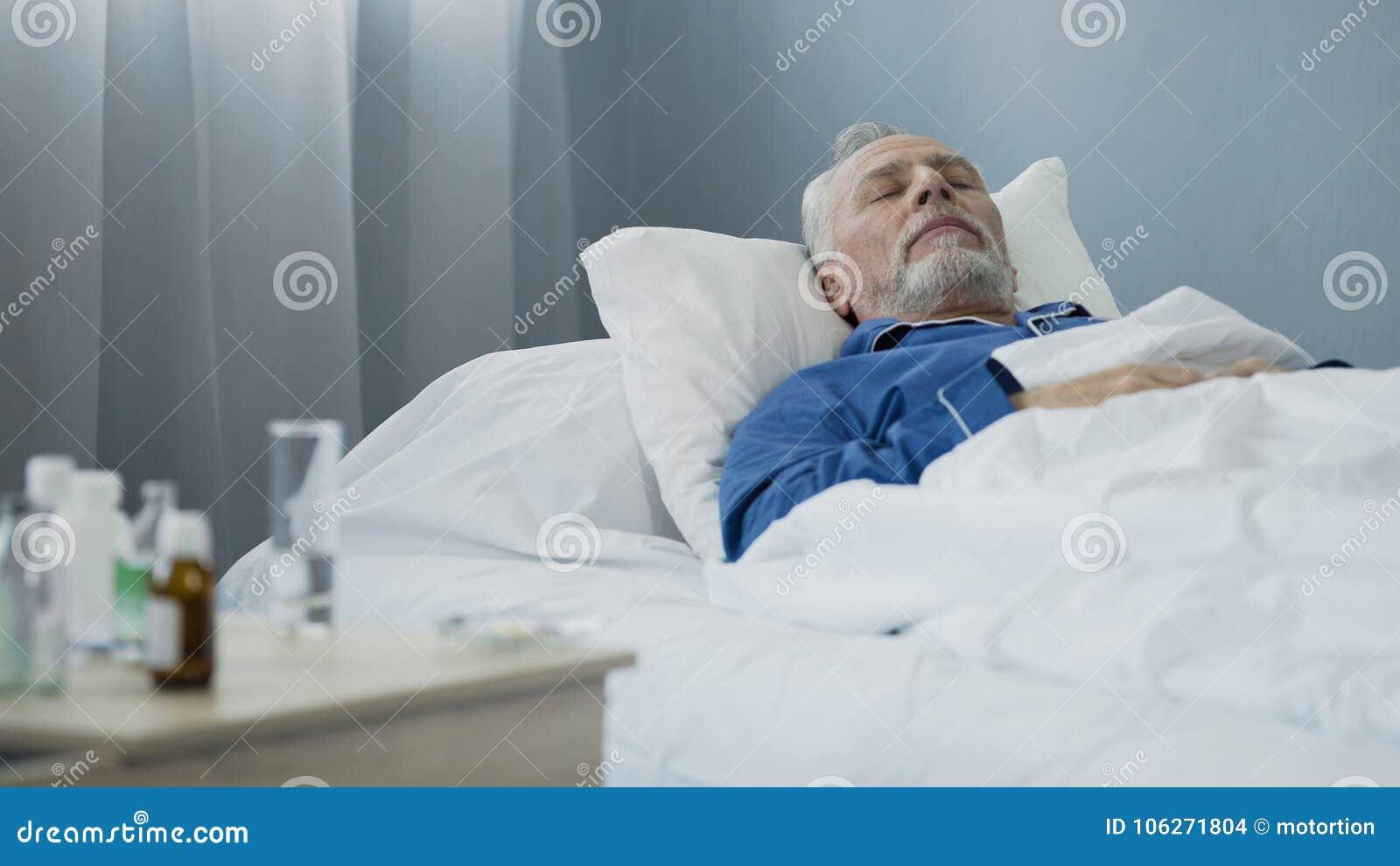 小睡在医院病床上的微弱的男性患者在采取疗程每日药量以后